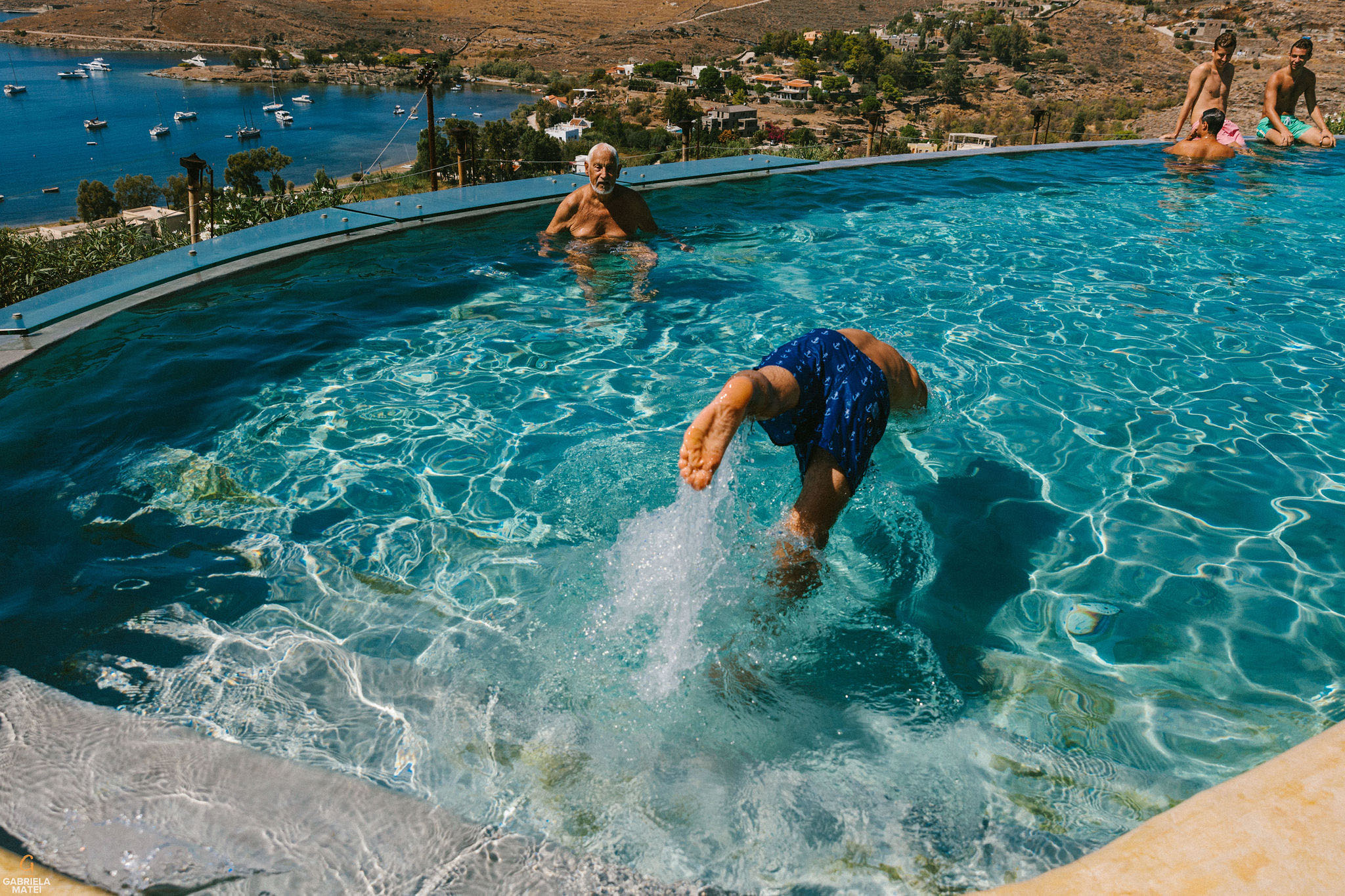 Groom jumping into the pool during bridal prep at Aigis Suites on Kea island