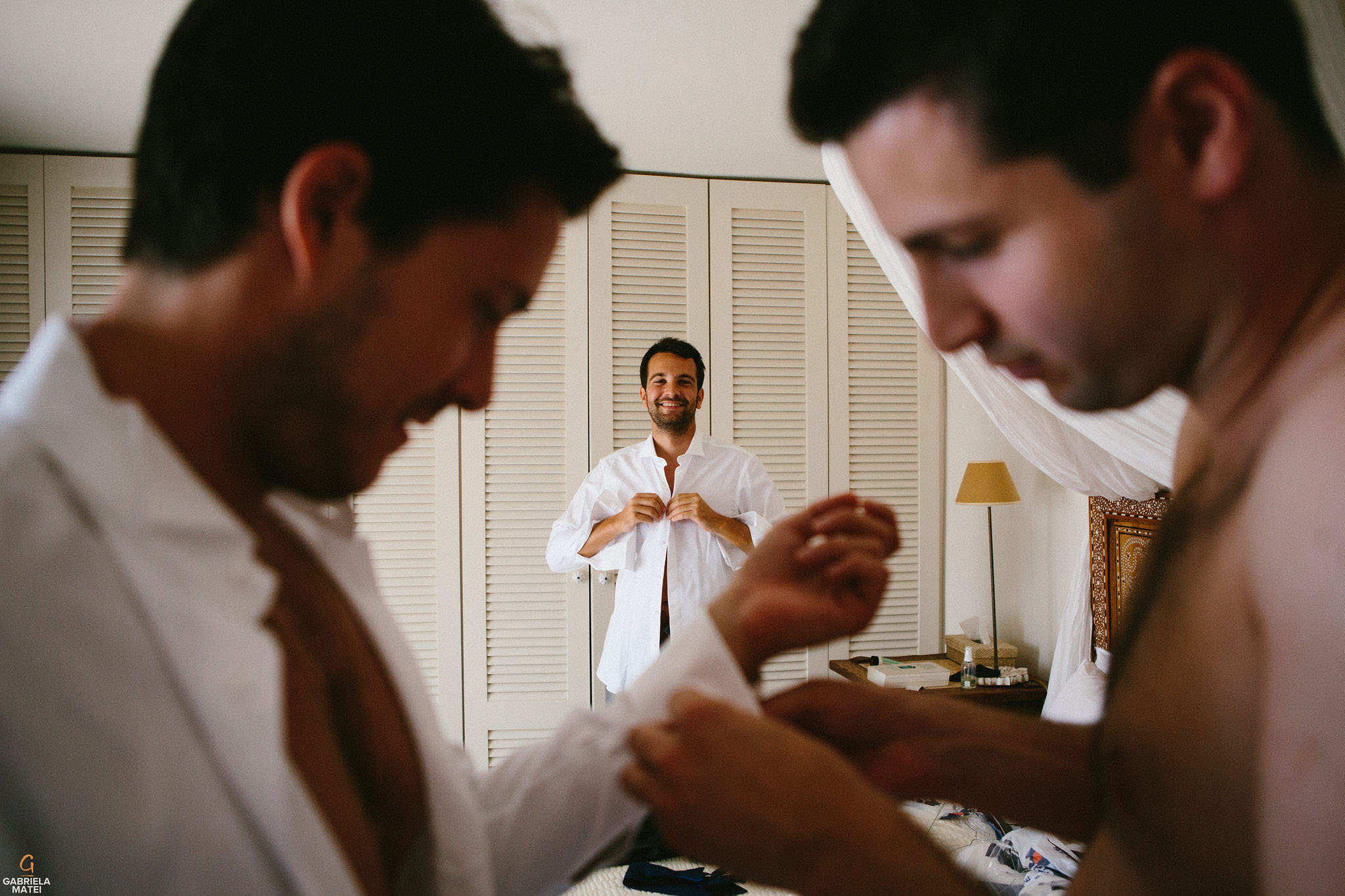 Groomsman buttoning his shirt during groom prep on Kea Island