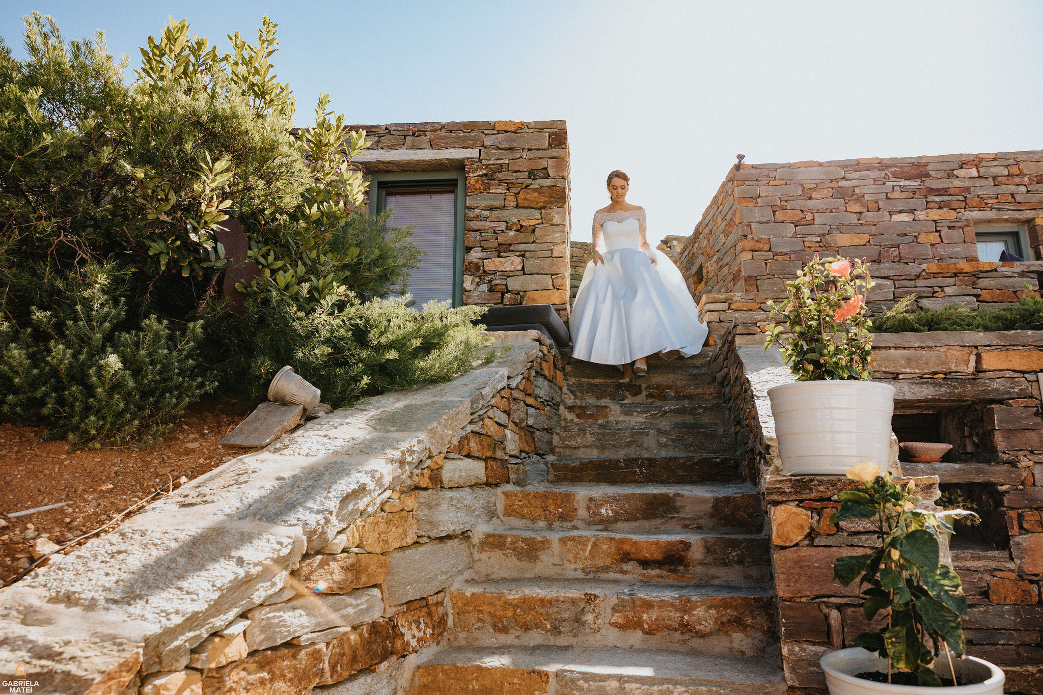 Bride holding her dress, coming down the stairs on Kea Island, Greece