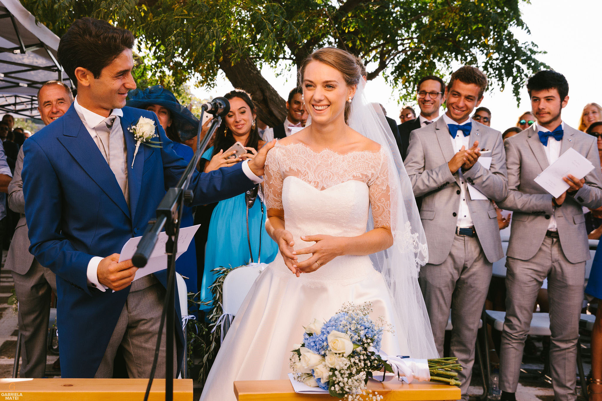 Groom touches Bride's shoulder during wedding ceremony on Kea Island