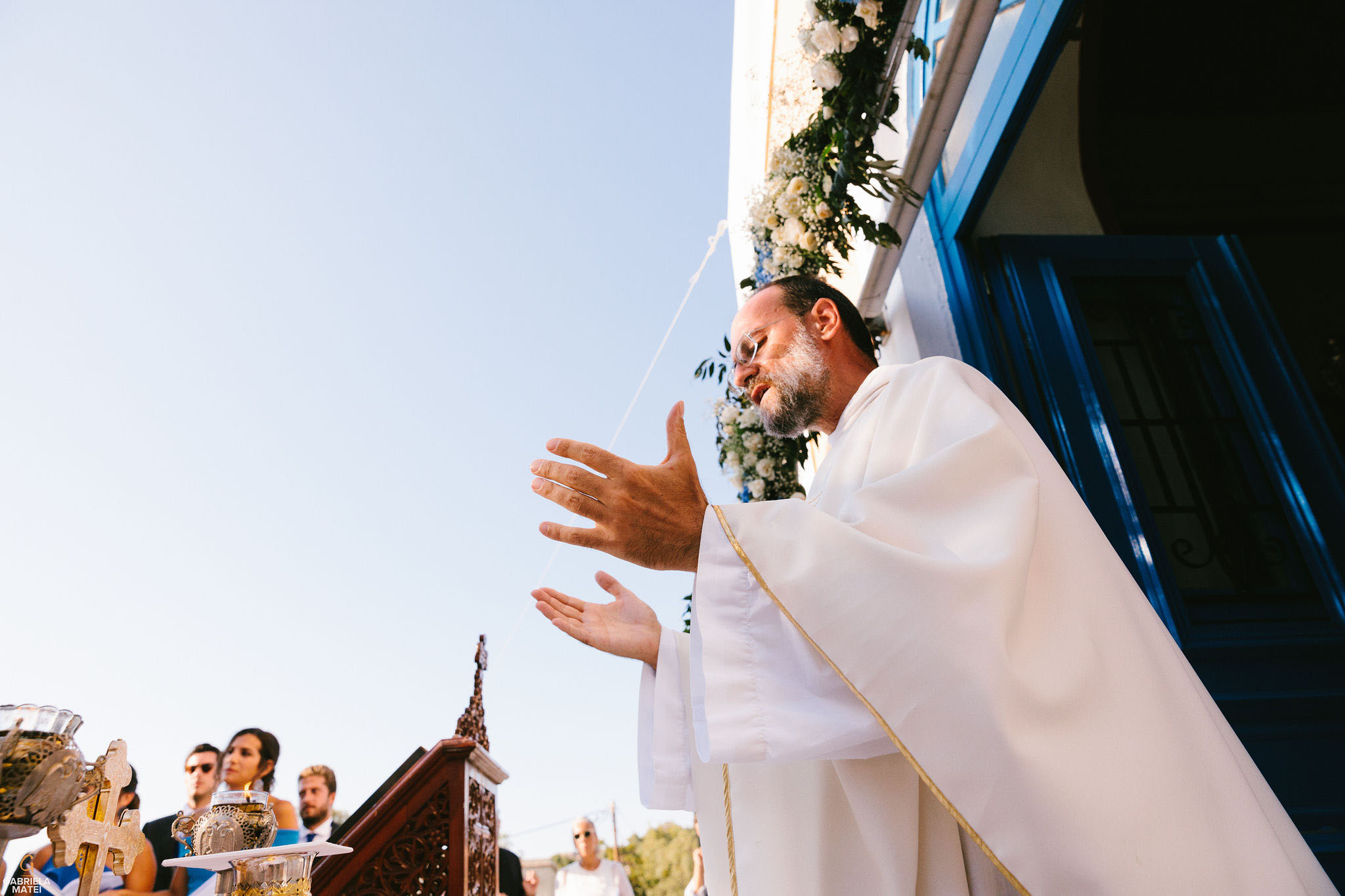 Preist praying with palms up in the air during wedding ceremony on Kea Island