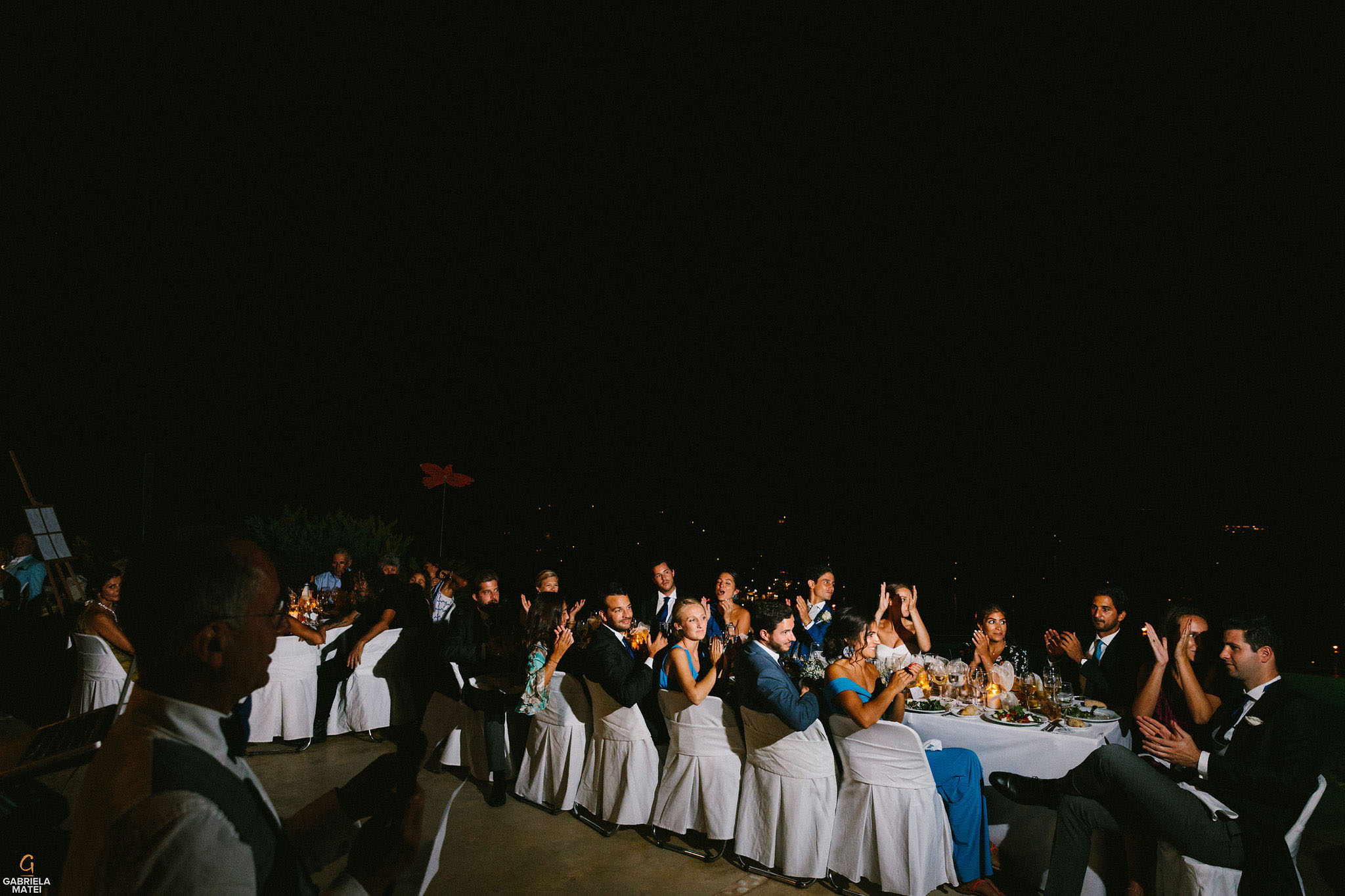 Wedding guest sat at long table outdoor at night