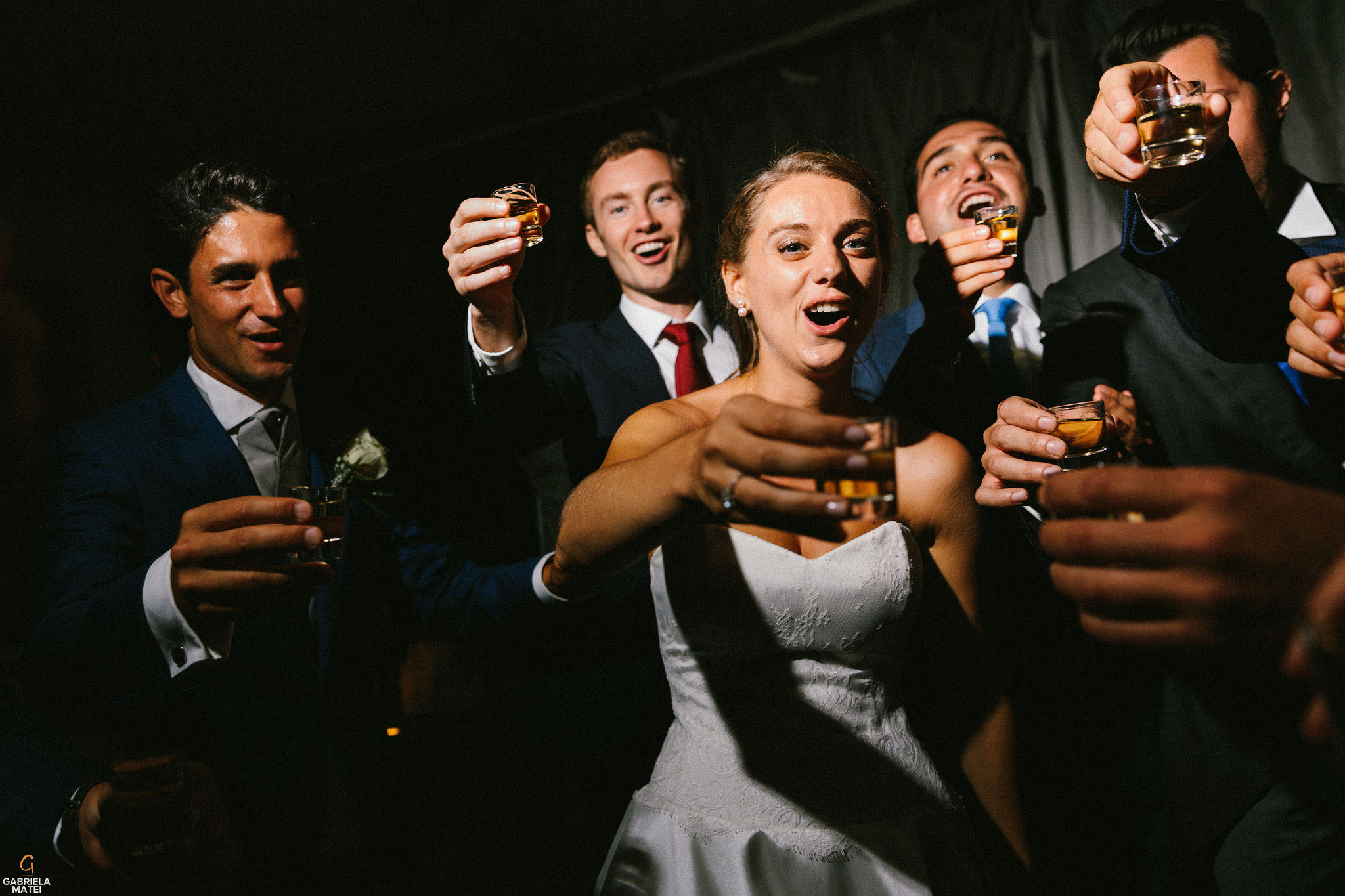 Bride drinking shots with wedding guests during wedding reception party