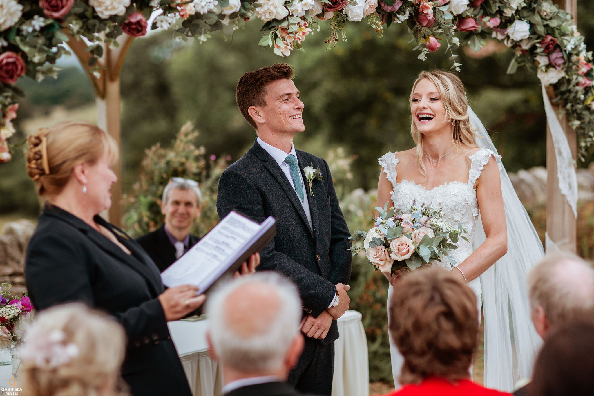 Bride and groom laughing during outdoor civil wedding