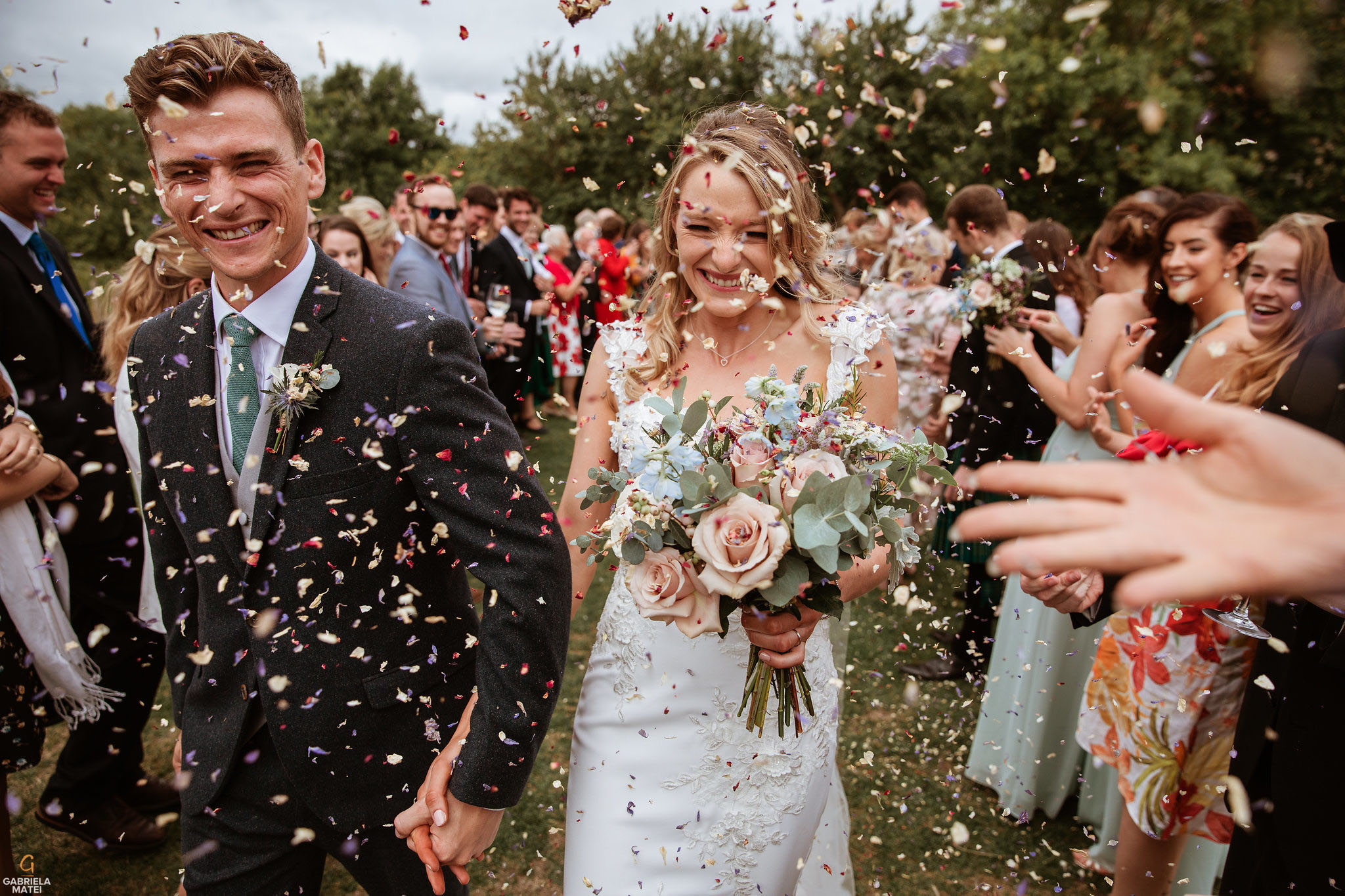 Wedding couple laughing whilst wedding guests throw confetti at them.