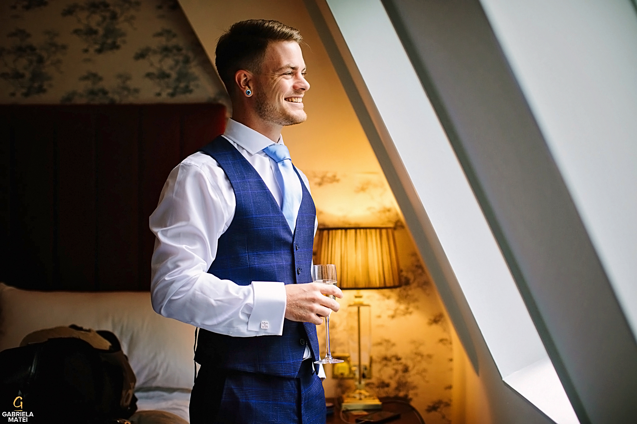 Groom looking out the window in hotel room in London