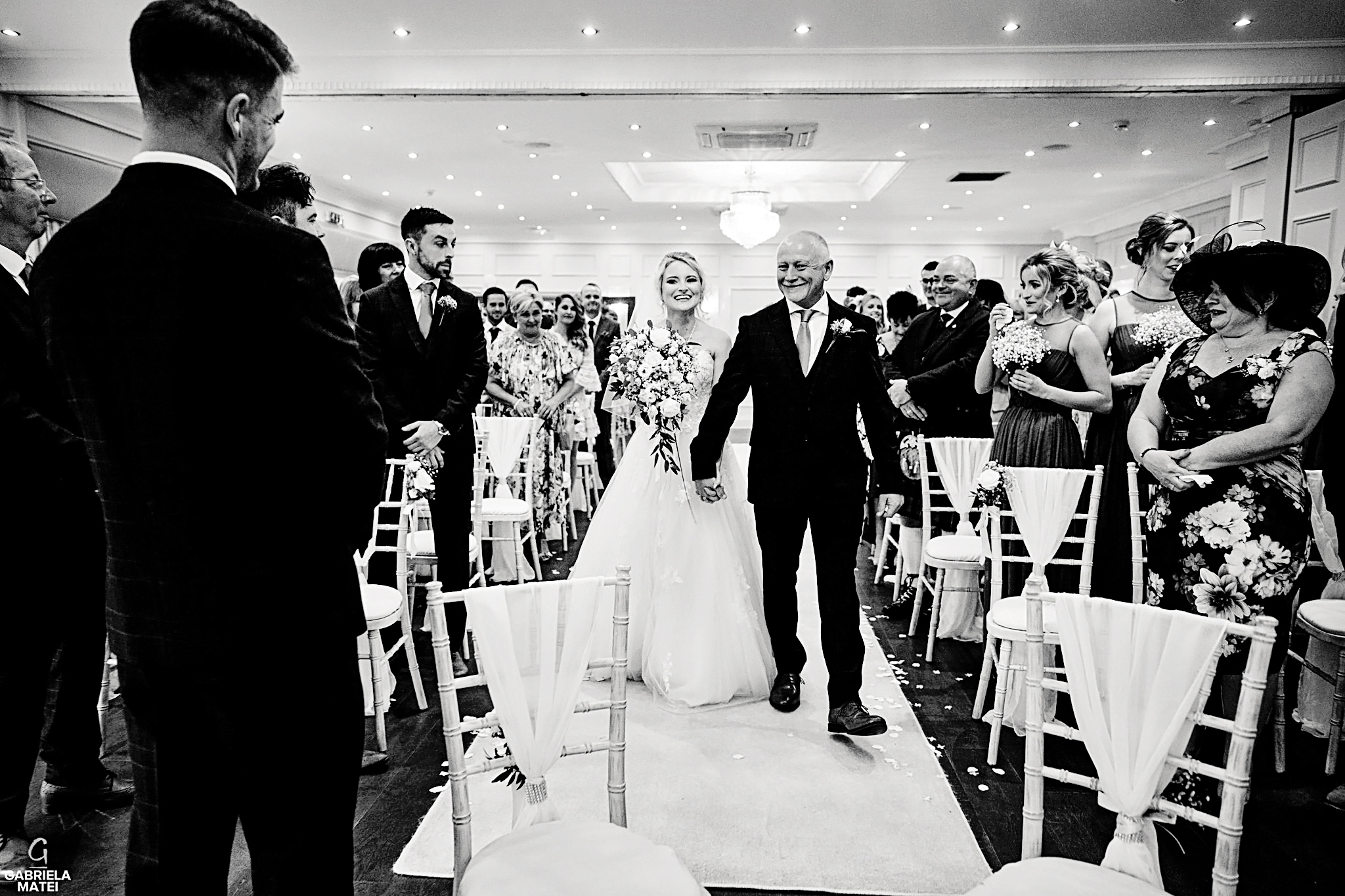 Bride walks up the aisle accompanied by her father at wedding venue in London
