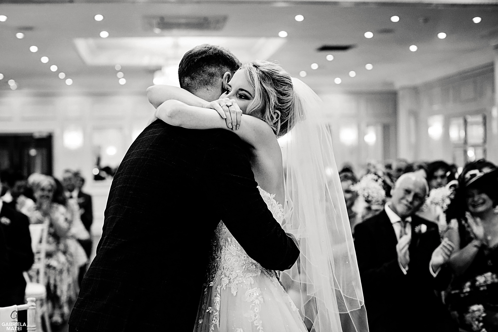 Bride and groom hug each other tightly during civil ceremony