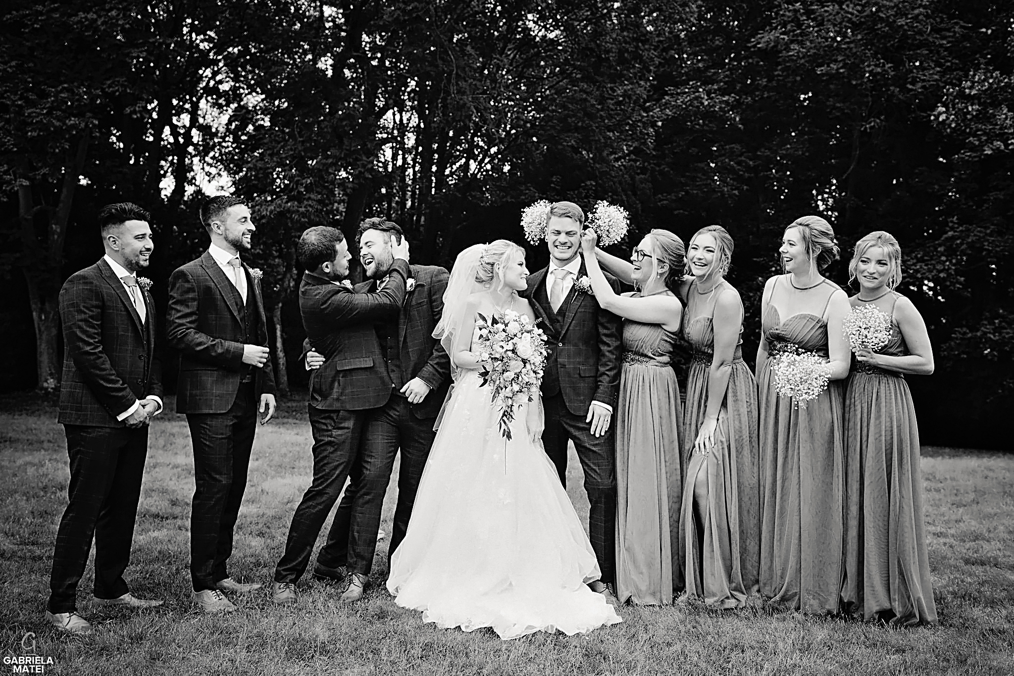 Bride and groom having fun with bridal party during group shots at wedding in London, outdoor group photos, fun photos