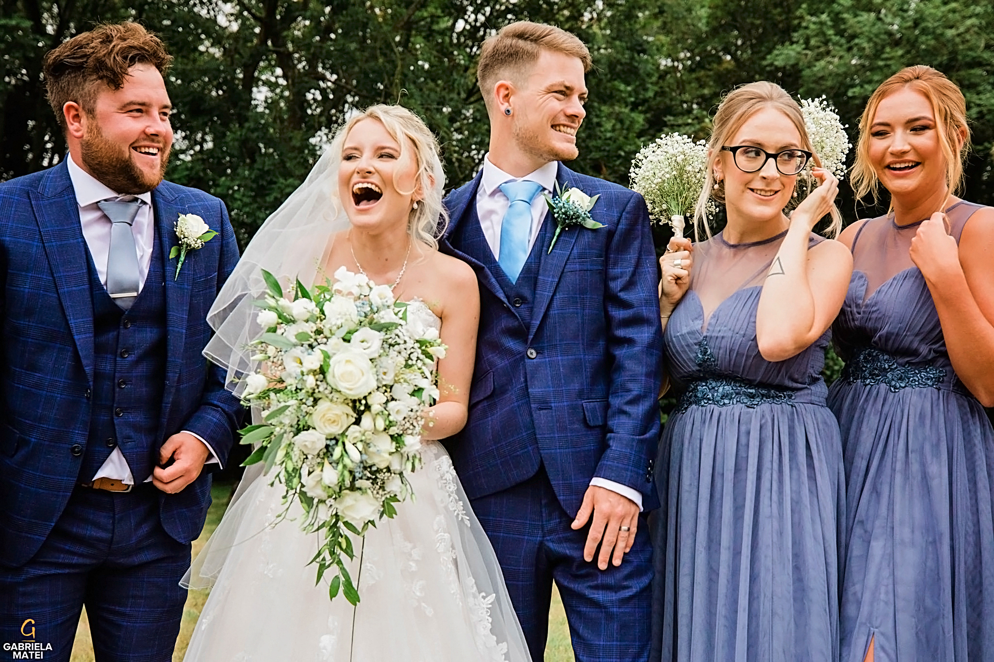 Bride cracks up laughing during group photos at wedding