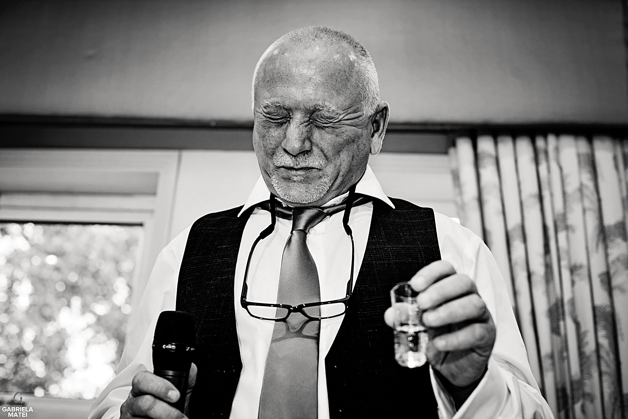 Father of the bride makes a grimasse after doing a shot during wedding reception