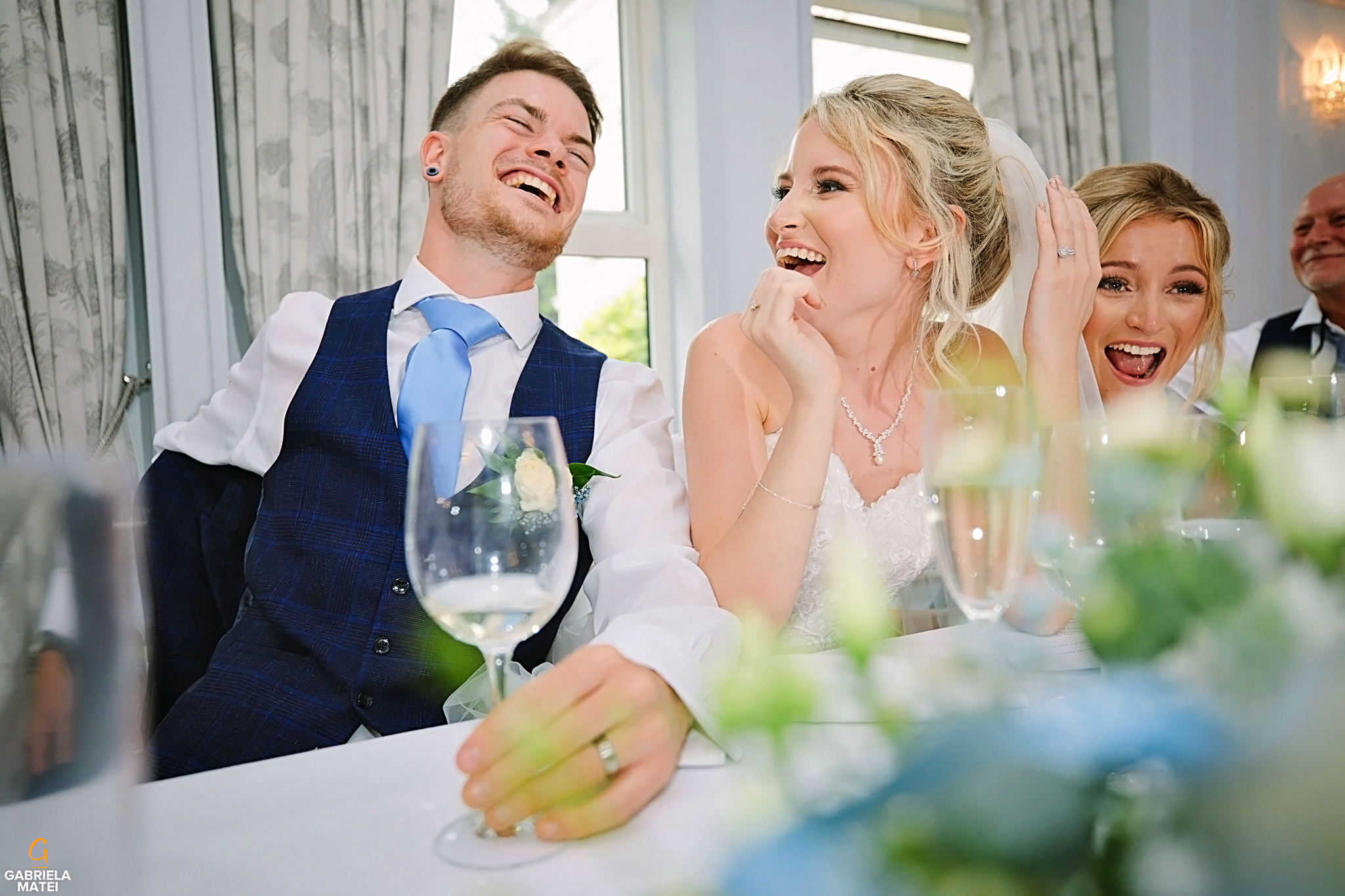 Bride and groom laughing during wedding speeches in London