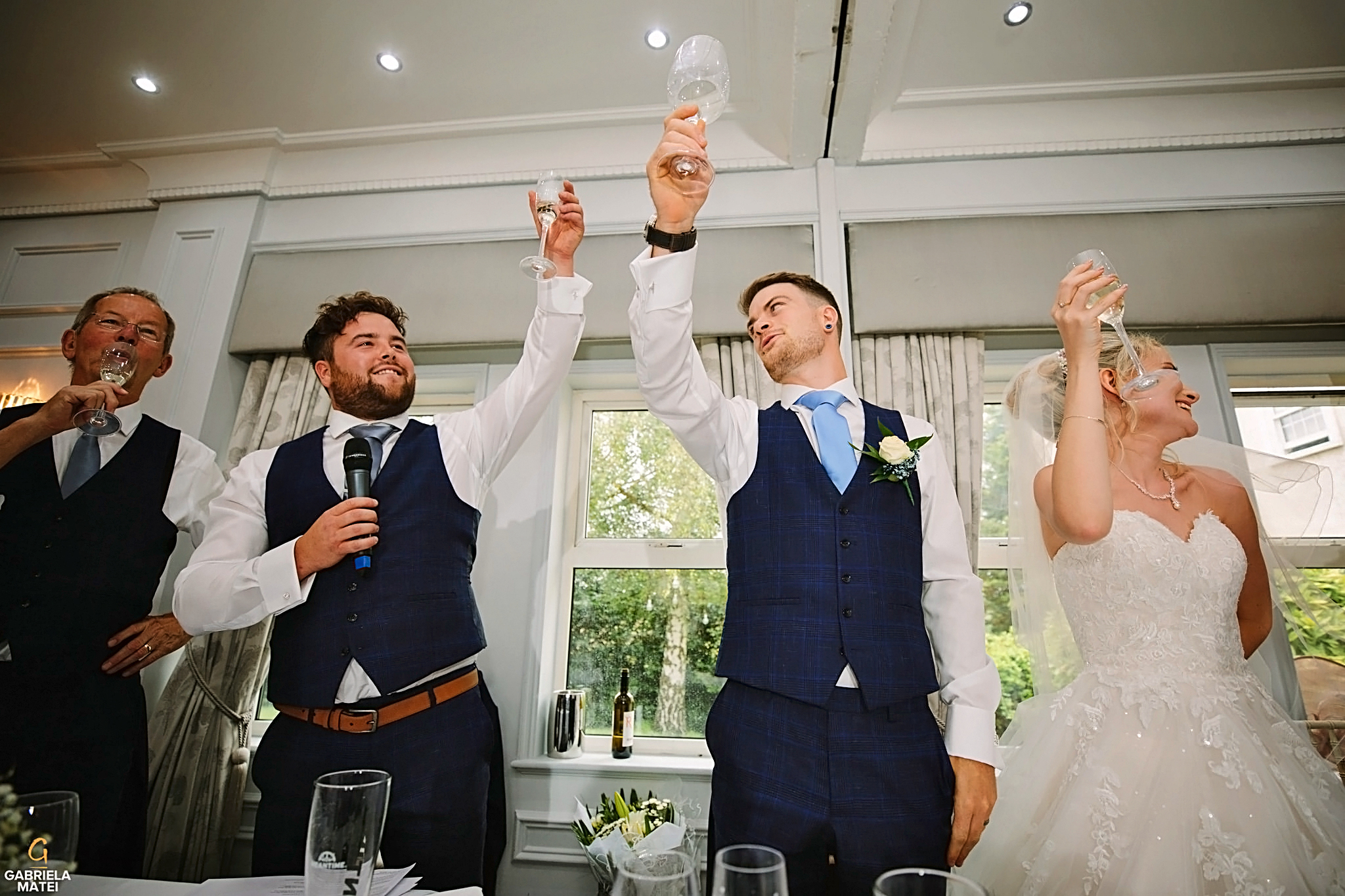 Groom and best man raising a toast during wedding speeches at wedding in London