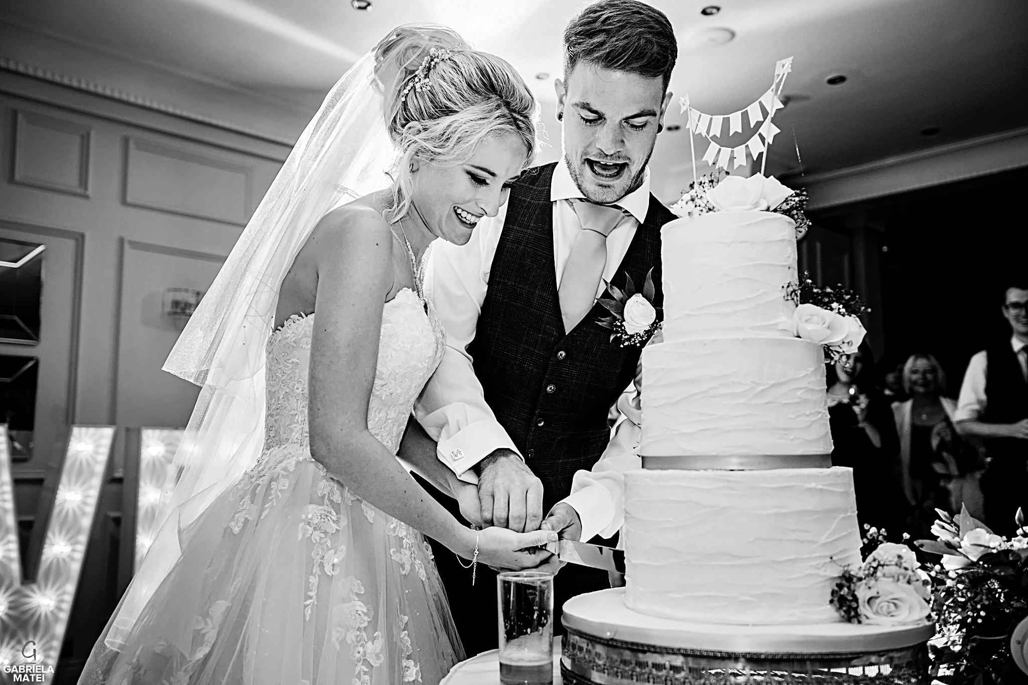 Bride and groom cutting the cake during wedding reception in London