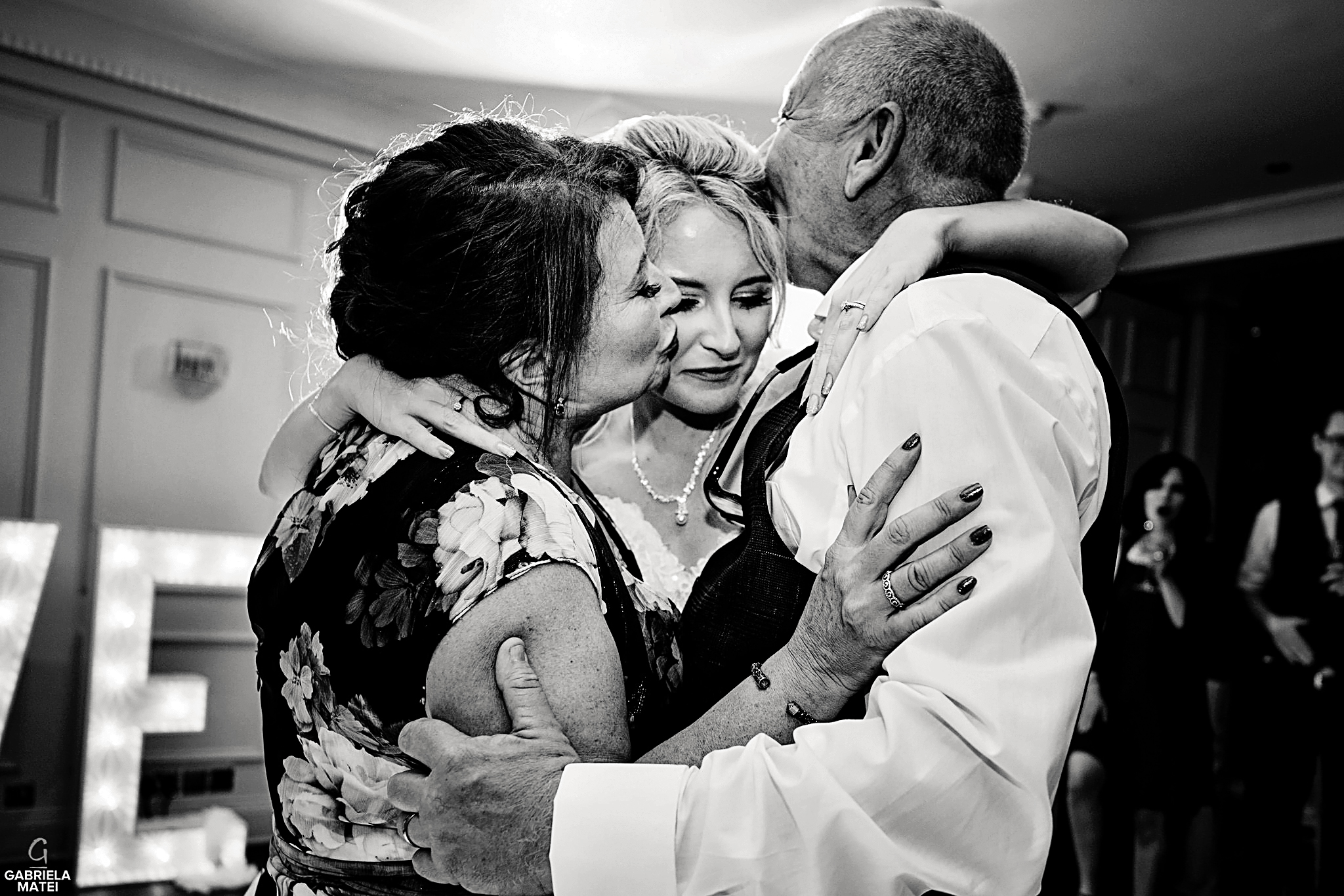 Mother and father of the bride hug her and give her a kiss during father-daughter dance at wedding reception in London