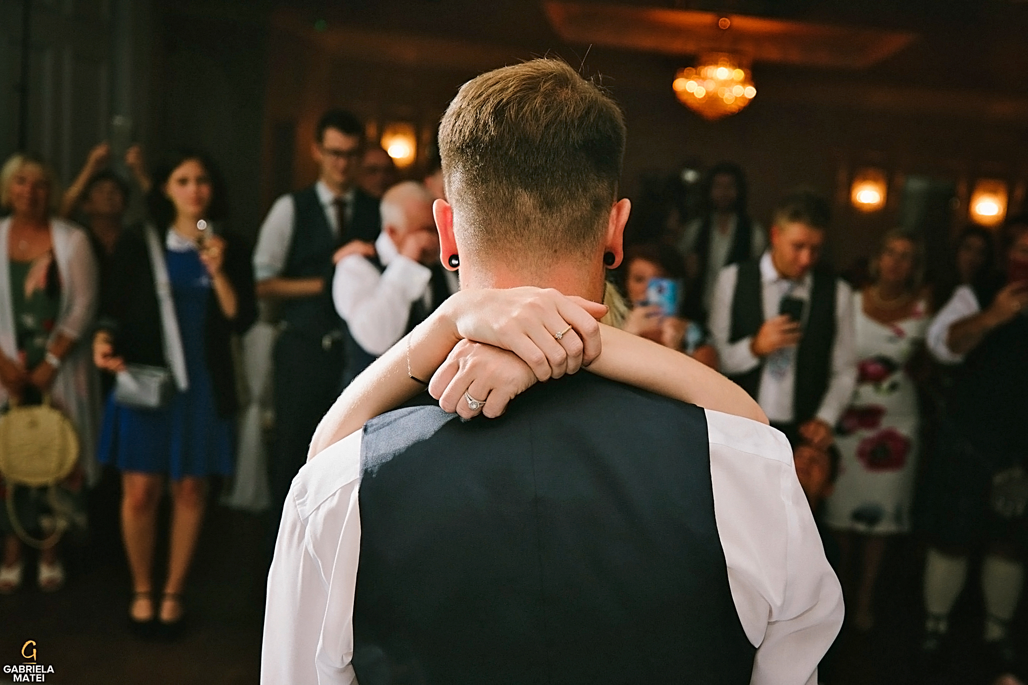 Bride places her hands on the groom's shoulders during first dance at wedding reception in LondonA