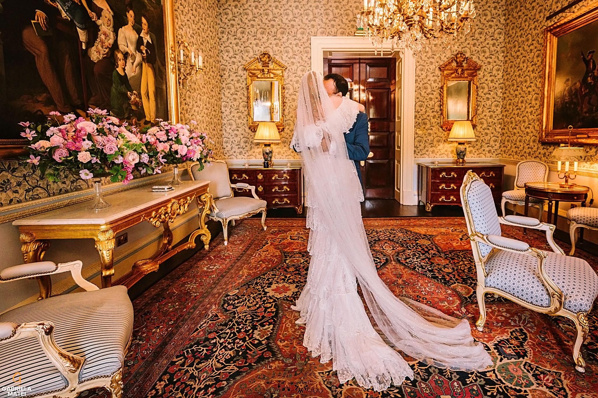 Bride and groom hug each other tightly during first look in Queen Elisabeth room at The Ritz hotel in London
