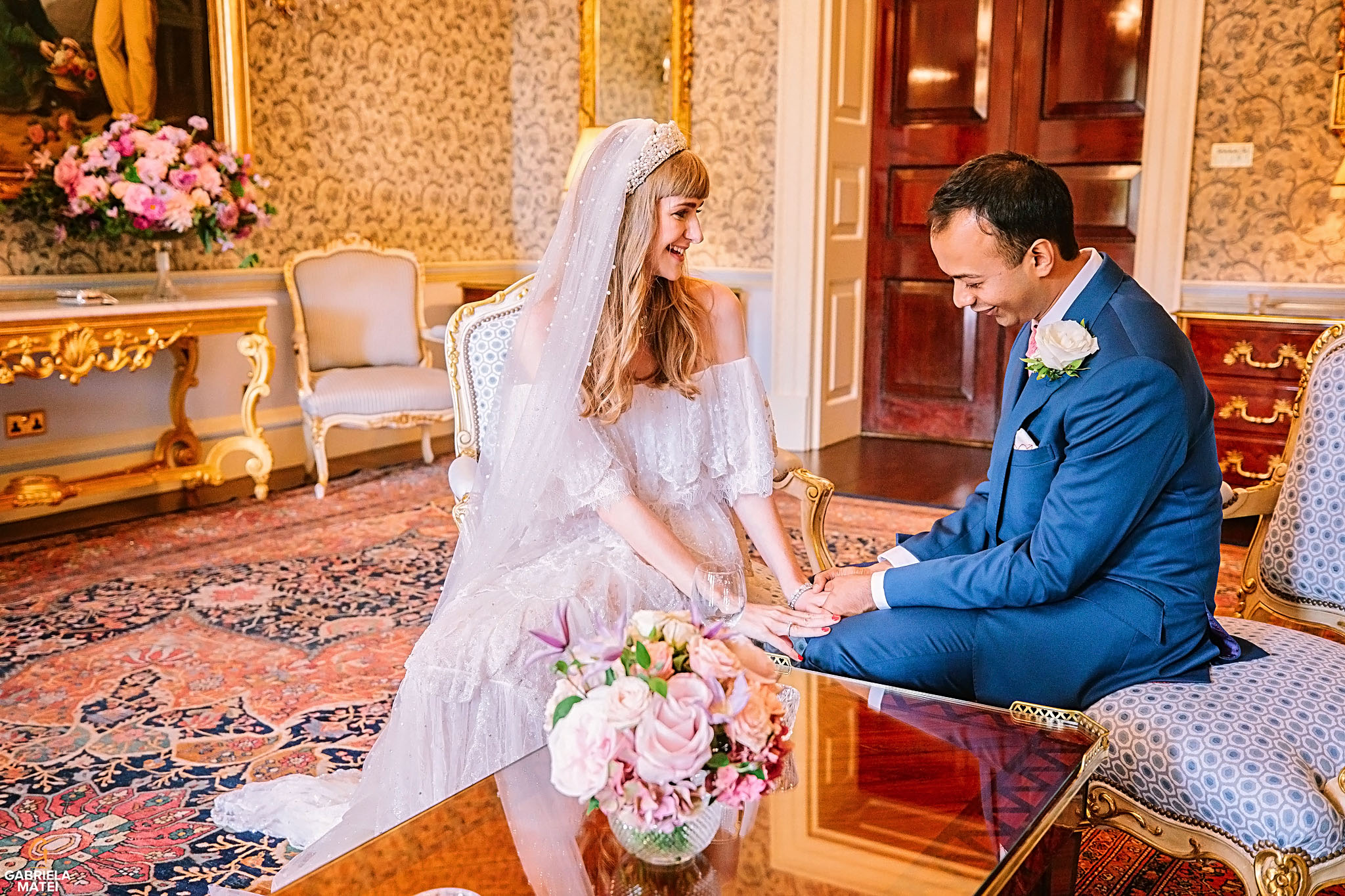 Bride and groom holding hands in Queen Elisabeth room at The Ritz hotel in London