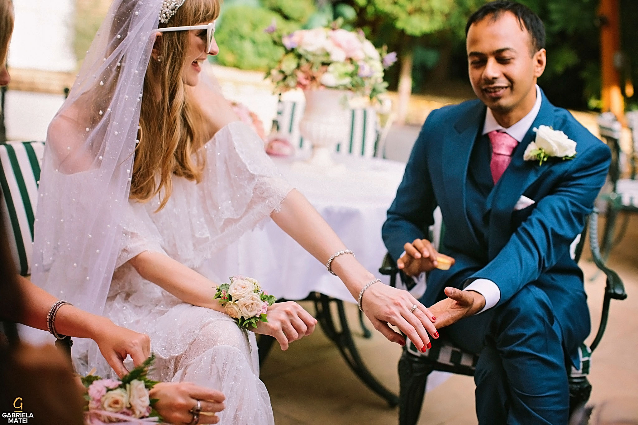 Groom holding bride's hand and looking at the wedding ring smiling in William Kent House Garden, The Ritz, London