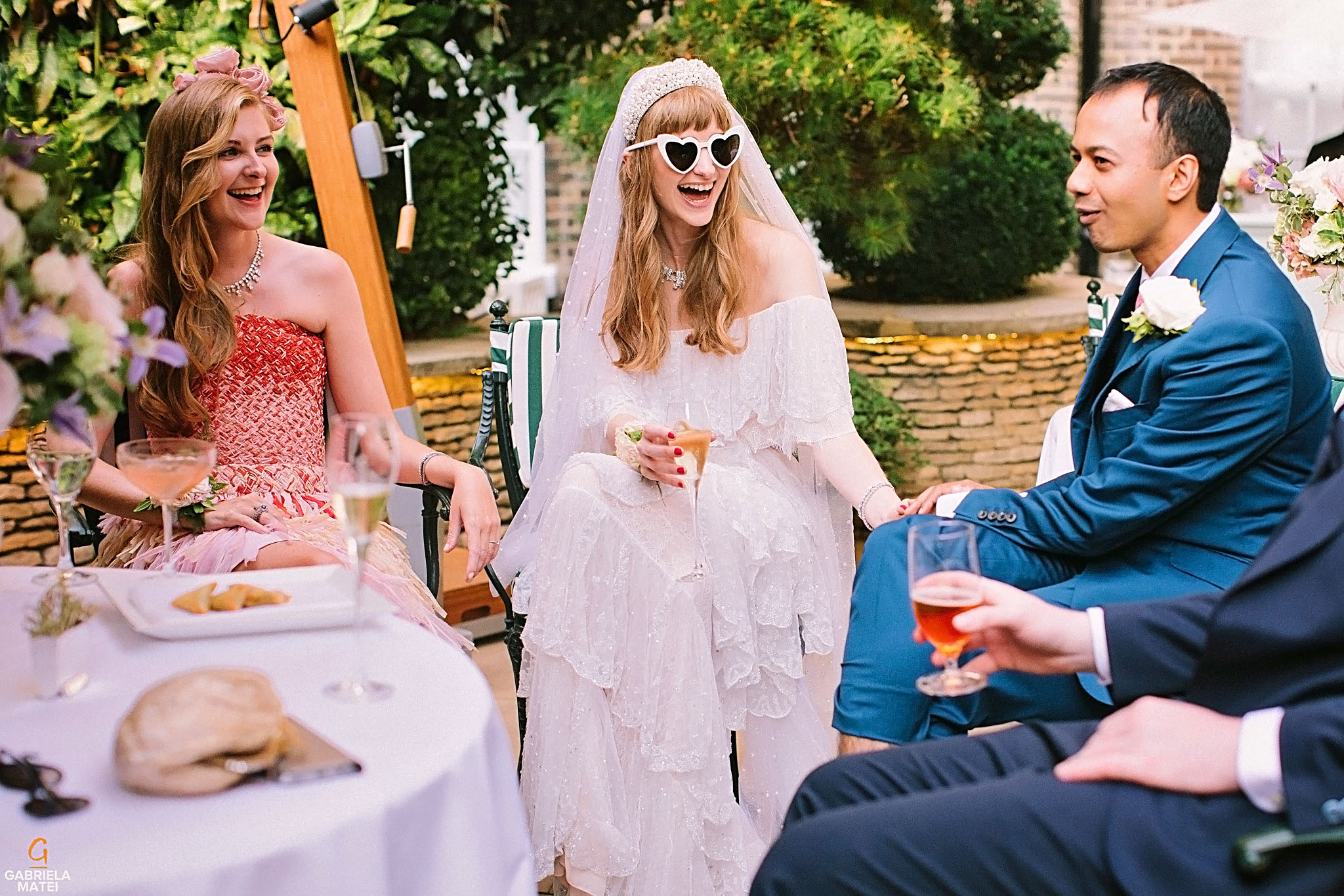 Bride and wedding guests laughing in William Kent House Garden at The Ritz Hotel