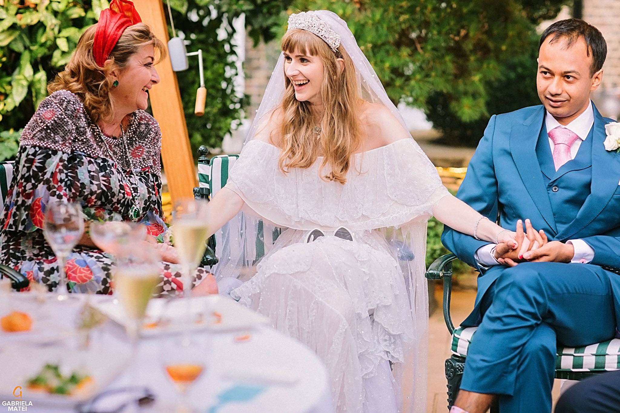 Bride laughing with wedding guests in outdoor garden, The Ritz