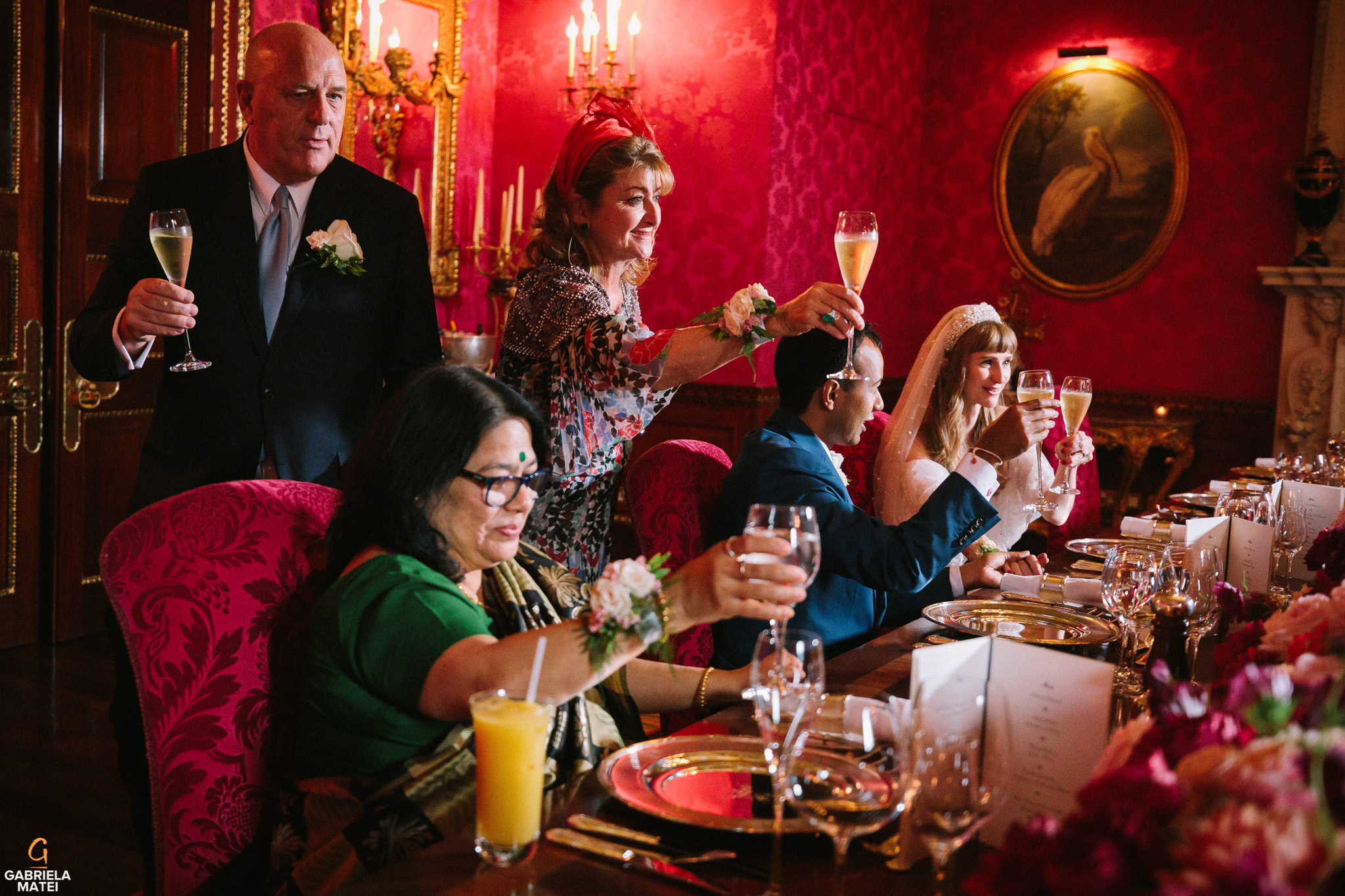 Wedding guests raising a glass for the married couple in Wiliam Kent House Room at The Ritz hotel in London