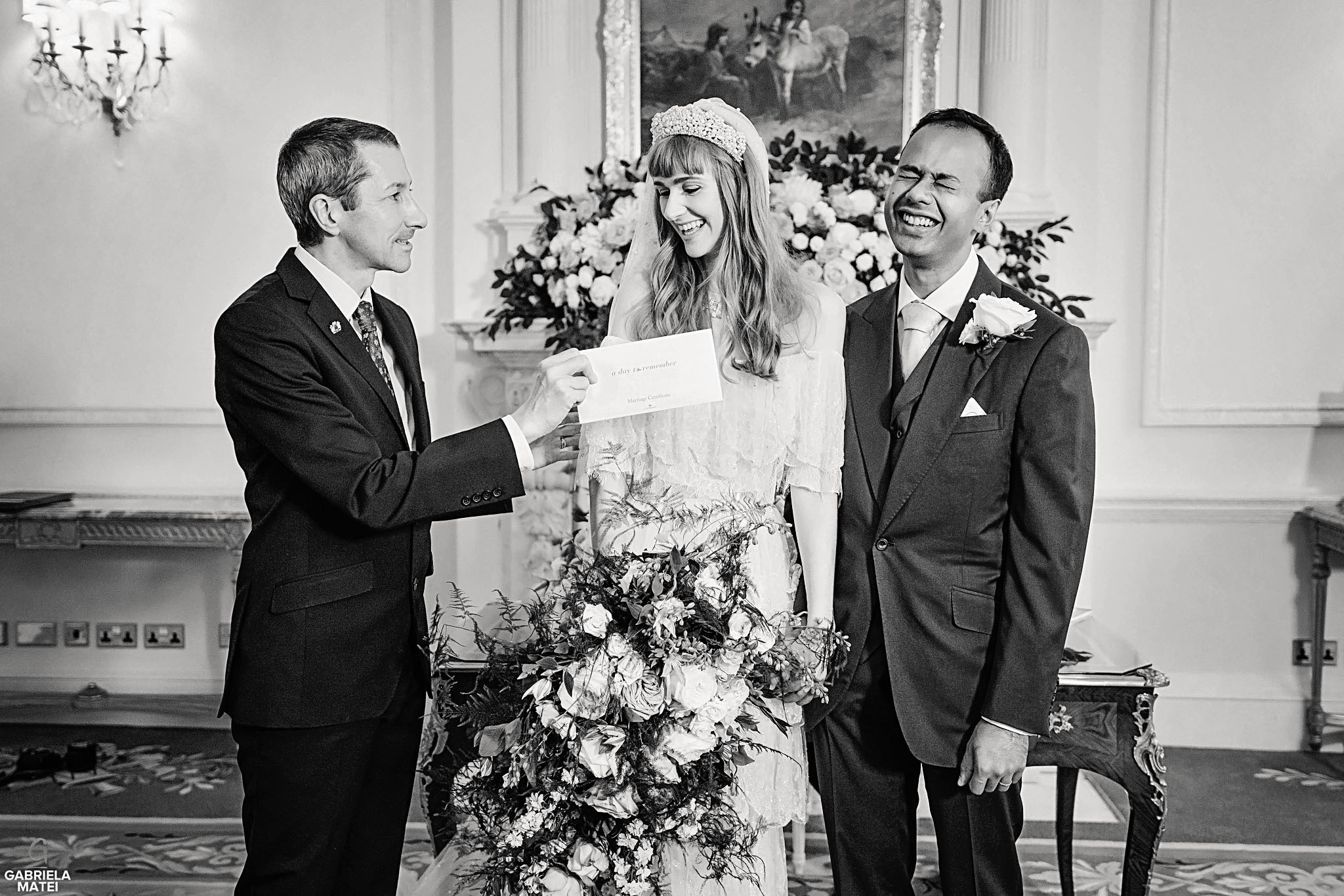 Bride and groom laughing whilst receiving the barrage certificate from the registrar during civil wedding at The Ritz Hotel in London