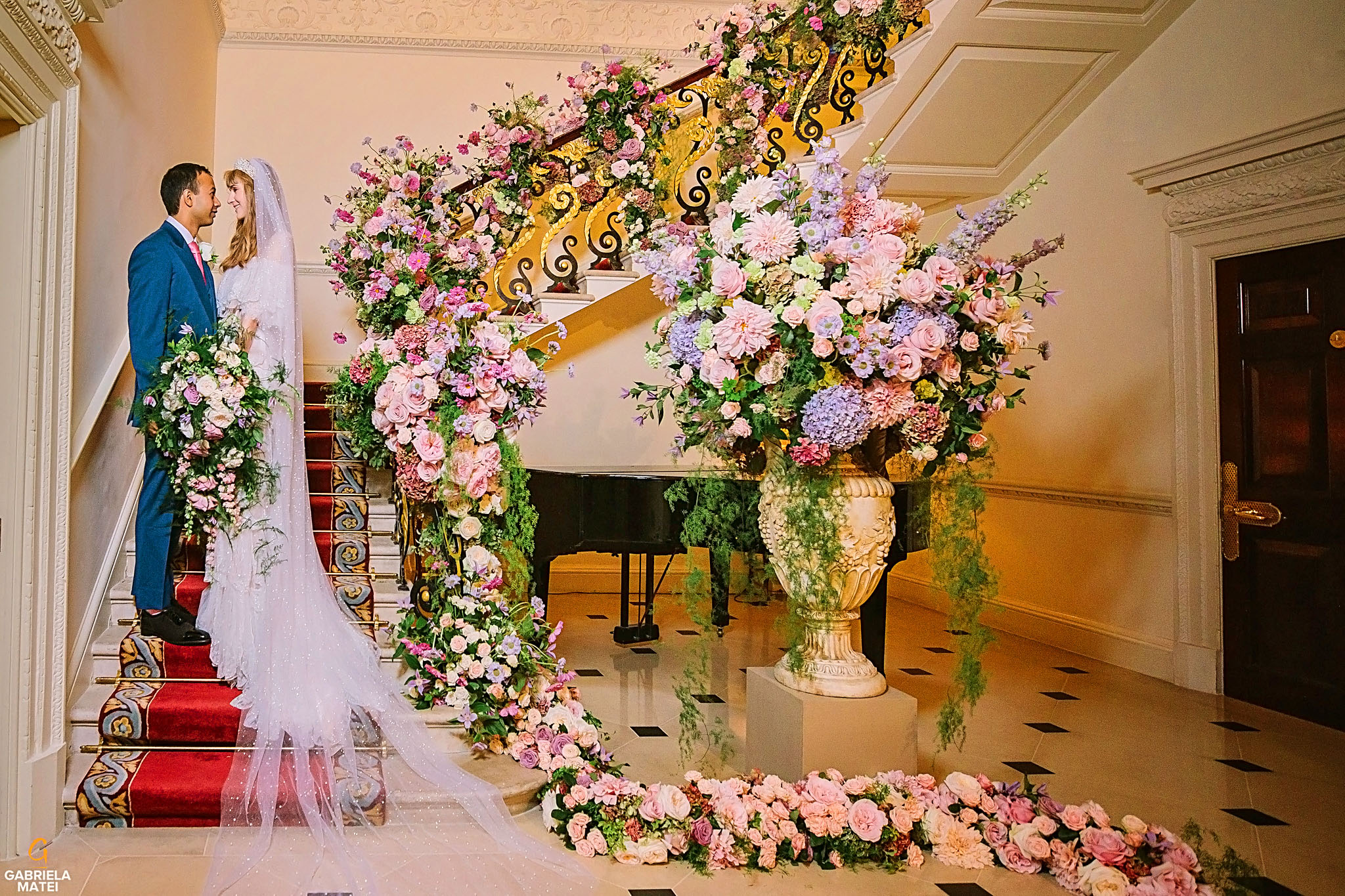Bride and groom on elegant staircase , decorated with stunning floral design