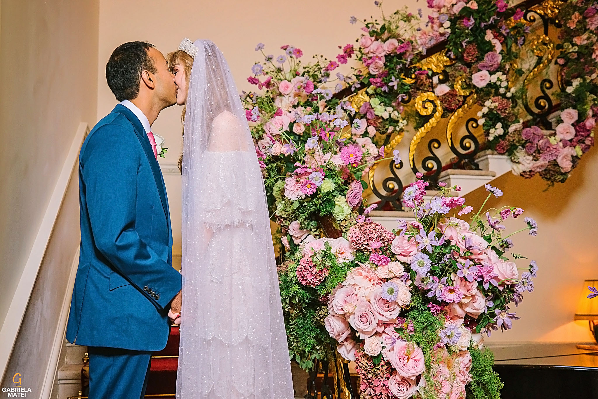Bride and groom kissing on beautiful staircase decorated with stunning wedding flowers at The Ritz Hotel