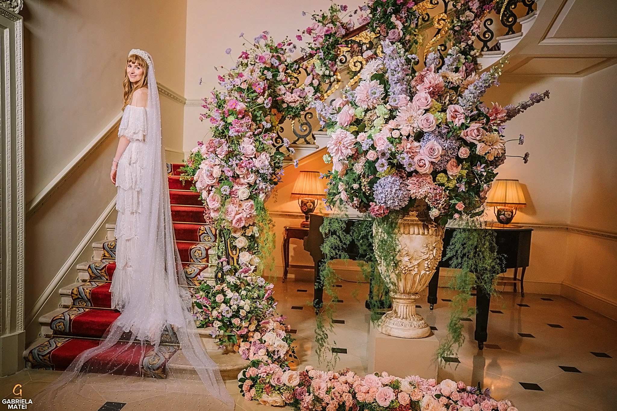 Beautiful bride on a staircase , wearing an elegant dress and a long veil in breathtaking wedding flower decor