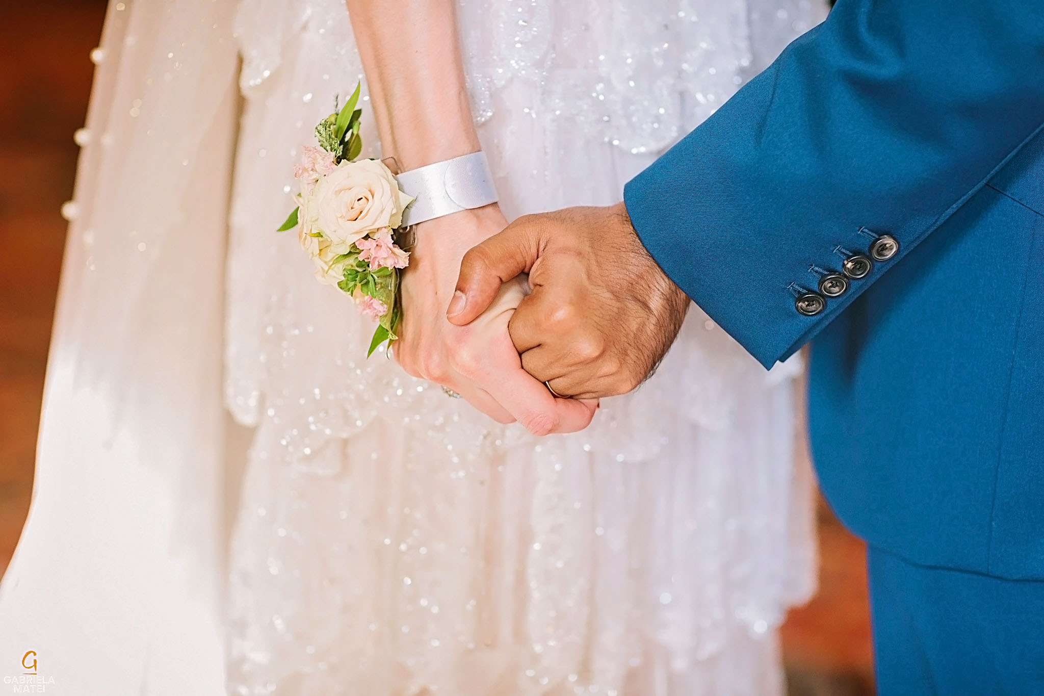 Delicate detail of wedding wrist corsage whilst bride and groom are holding hands