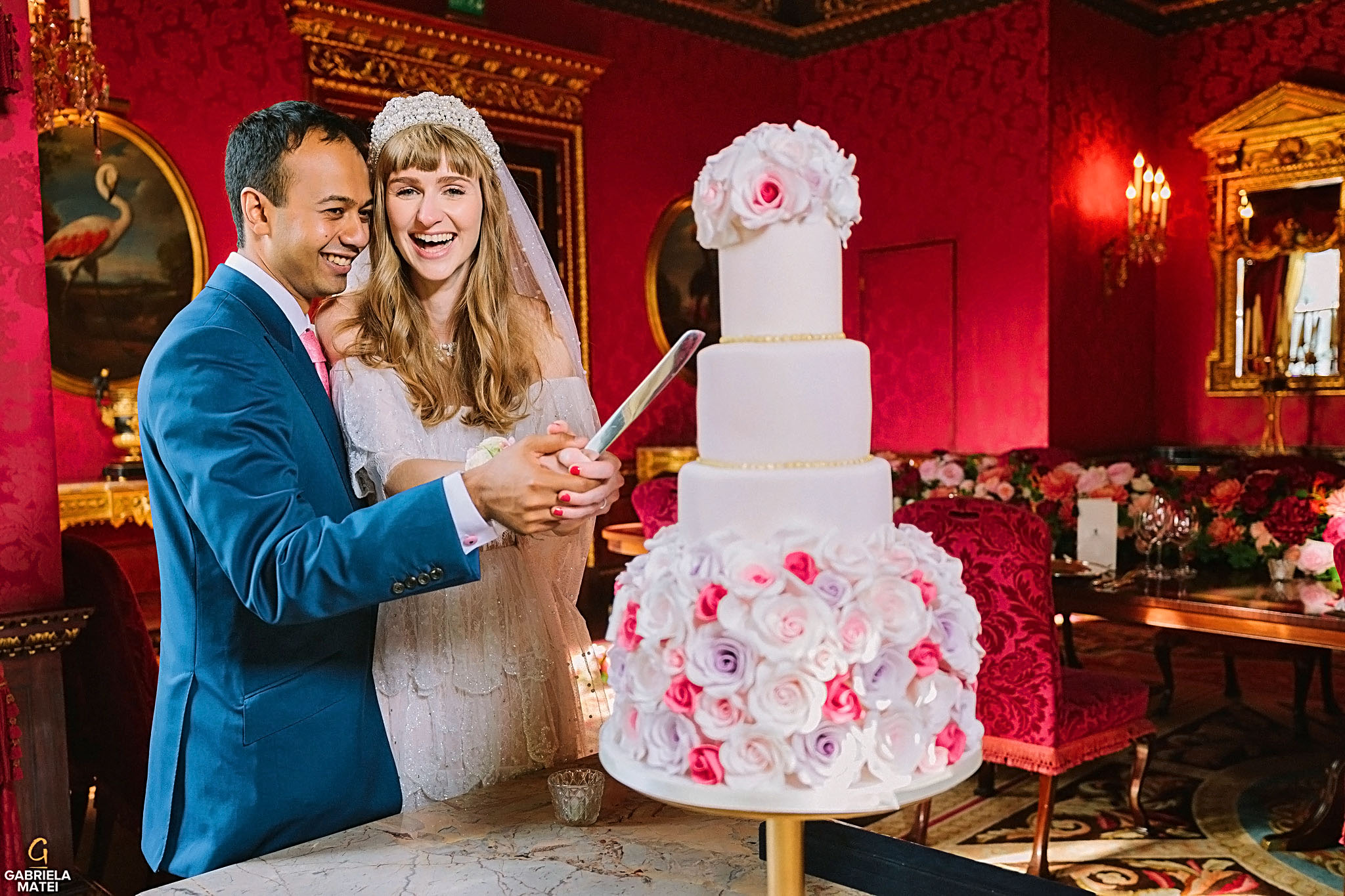 Bride and groom cutting an elegant cake , decorated with beautiful flowers, in William Kent House Room at The Ritz hotel in London