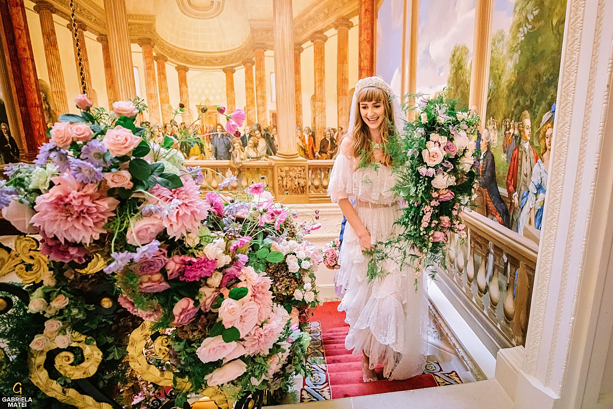Bride walking up the Ritz hotel staircase , holding up an elegant floral bouquet