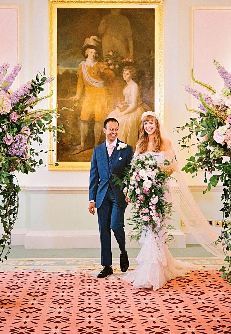 Bride and groom walk down the aisle together during civil wedding that takes place in the Music Room at The Ritz Hotel in London