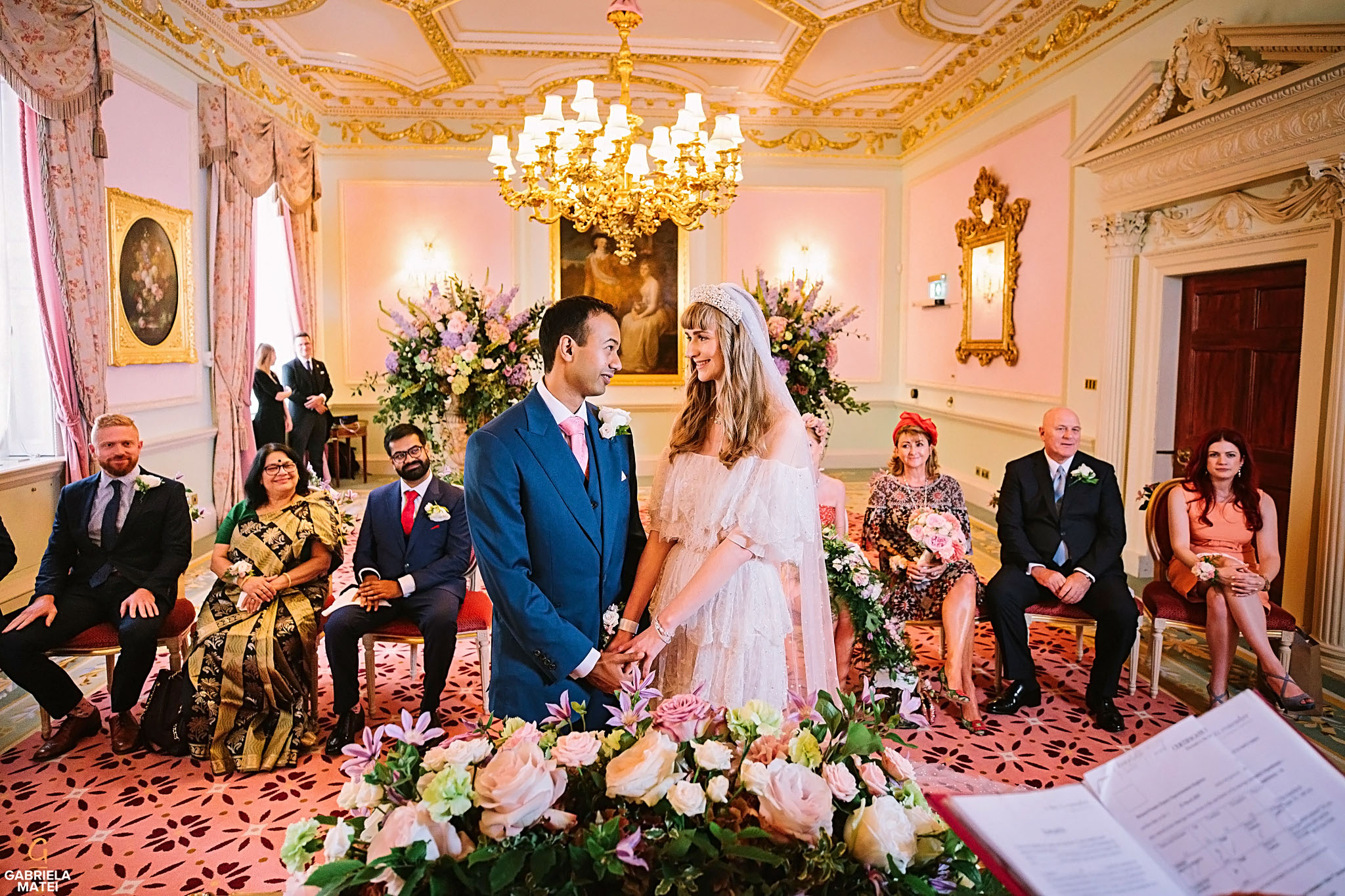 Bride and Groom holding hands and looking into each other's eyes during civil wedding at the Ritz hotel London