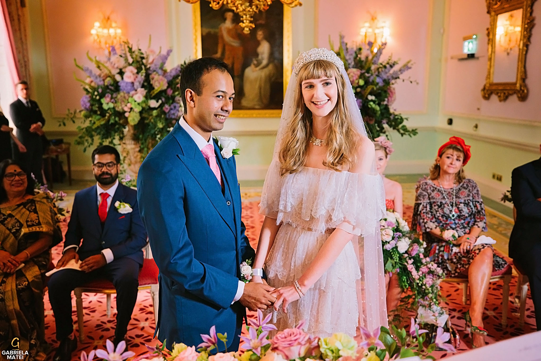 Bride and groom holding hands and looking towards the registrar during civil wedding in the Music Room at The Ritz Hotel in London