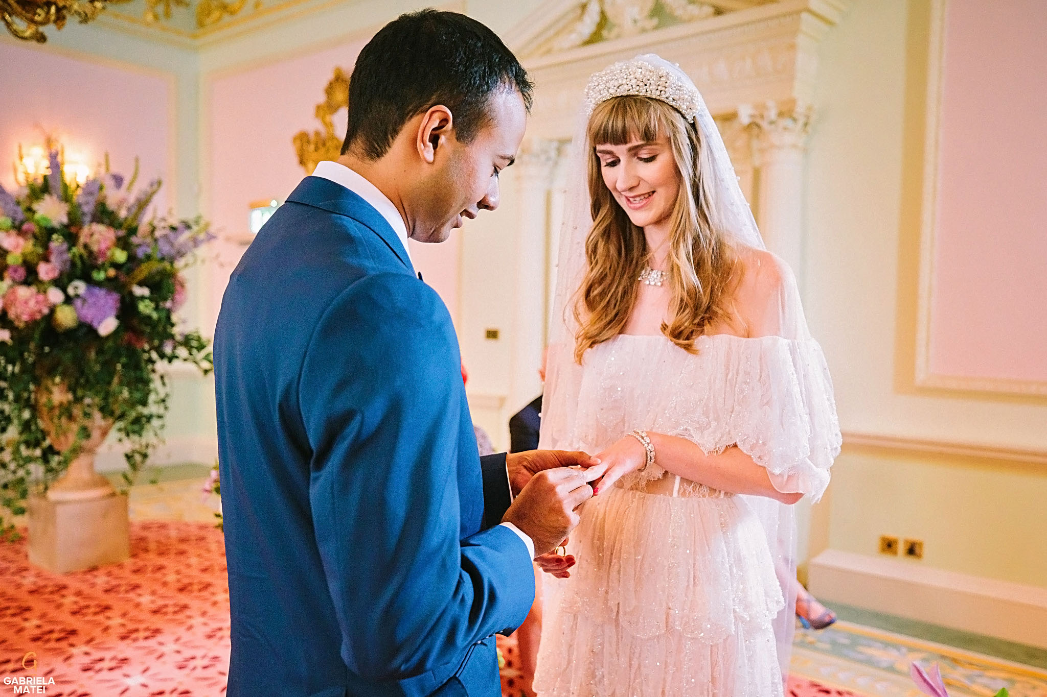 Groom placing the ring on the bride's finger during civil ceremony at The Ritz Hotel in London