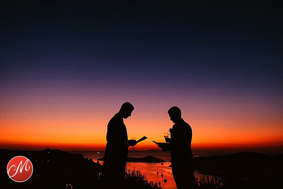 Grooms men reading their speeches with stunning sunset over the sea in the background during wedding in Cyclades Islands, Kea, Greece