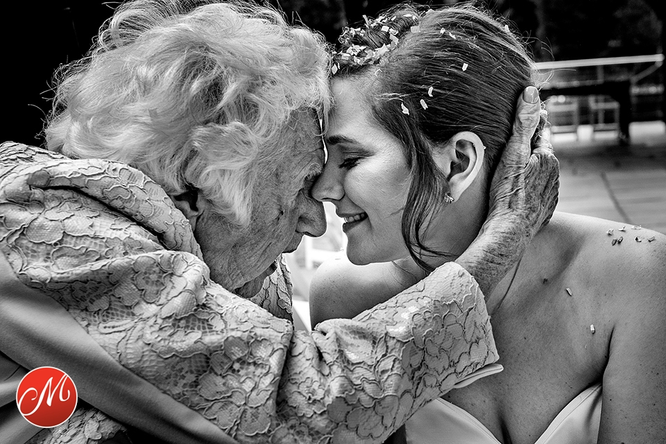 Grandmother and bride, head to head, hugging each other creating a very emotional moment at wedding in West Sussex