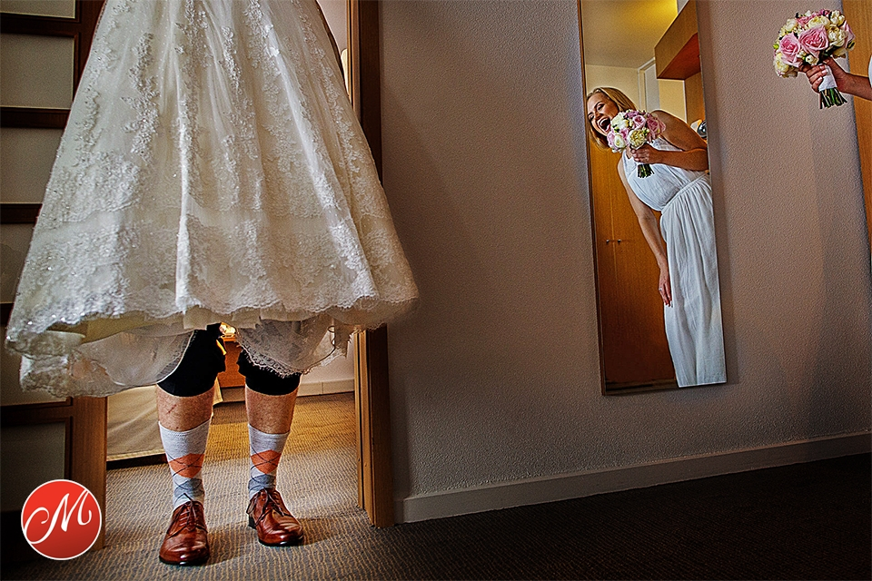 Groom hiding behind the wedding dress while bride cracks up laughing at wedding in Worthing, West Suusex