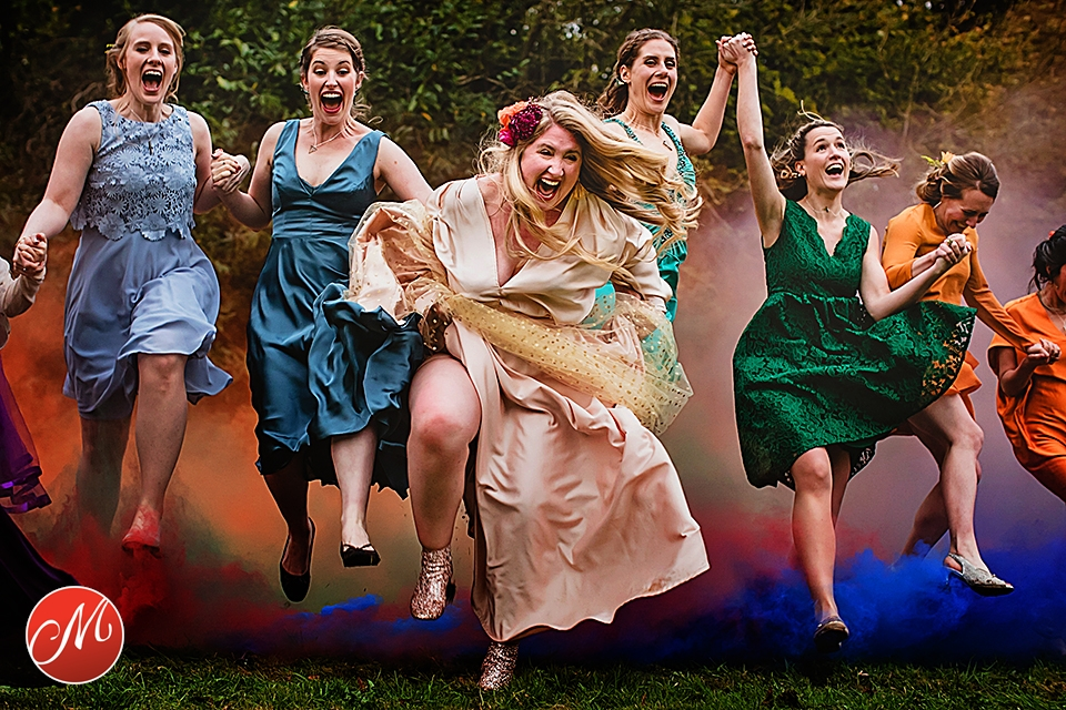 Bride and bridesmaids running across the field, jumping over smoke bomb' smoke during wedding in West Sussex