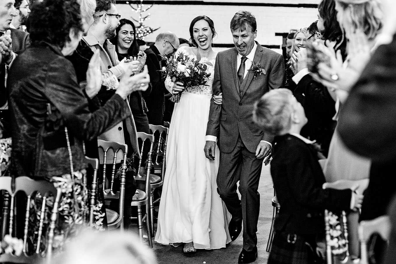 Bride walking down the aisle along side her father, whilst guests are clapping their entrance at Lillibrooke Manor and Barns wedding venue