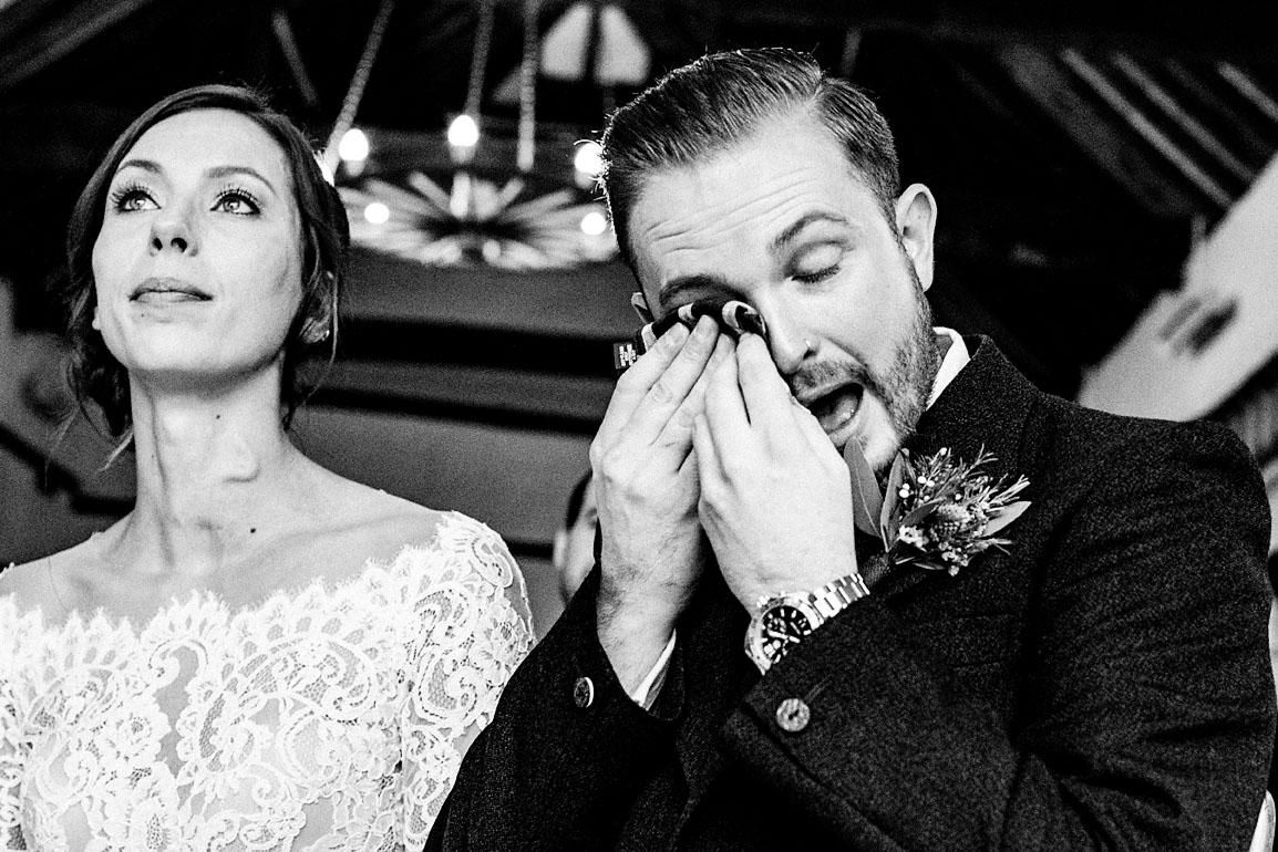 Groom uses his scarf to wipe his tears away during emotional during a reading at alternative wedding ceremony at Lillibrooke Manor and Barns