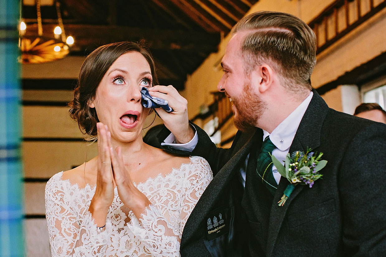 Groom uses a scarf to wipe his bride's tears away during alternative wedding ceremony at Lillibrooke Manor and Barns