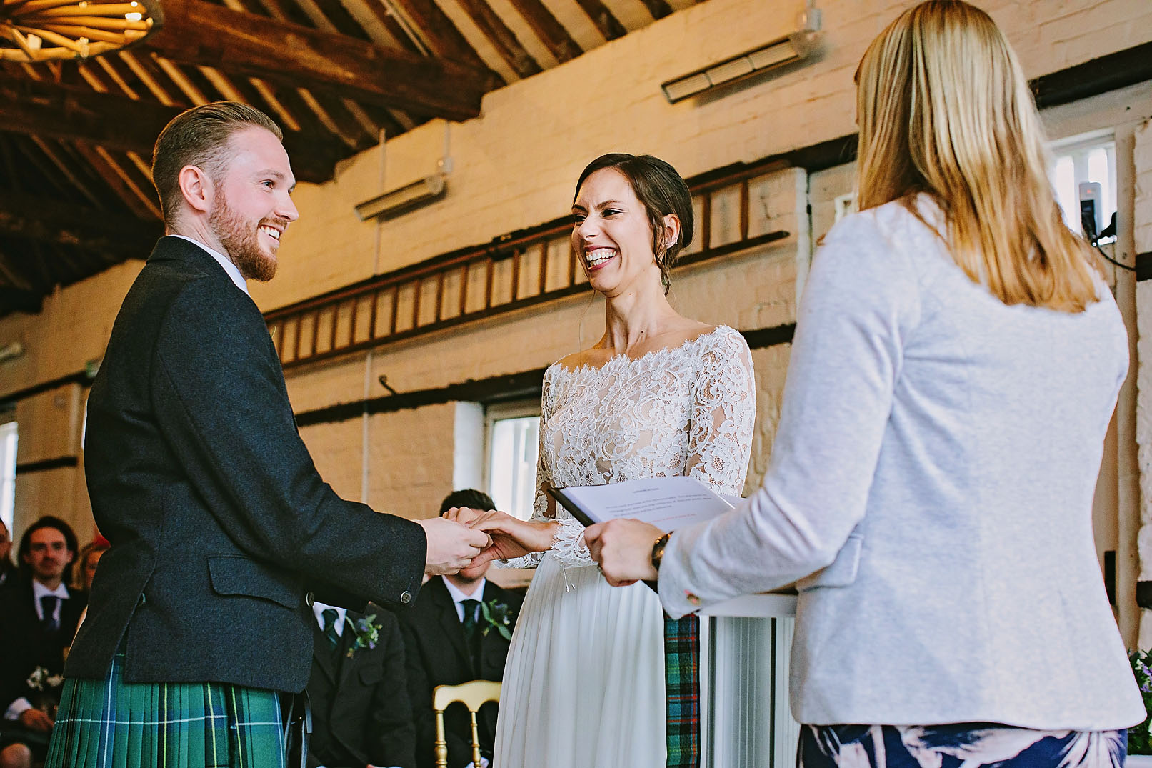 Bride and groom holding hands during marriage vows at their wedding in Berkshire, Lillibrooke Manor & Barns