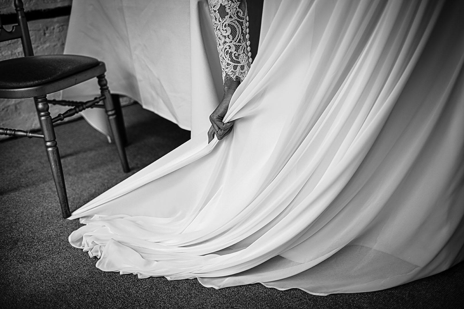 Detail of bride's dress caught underneath a wedding chair's leg.