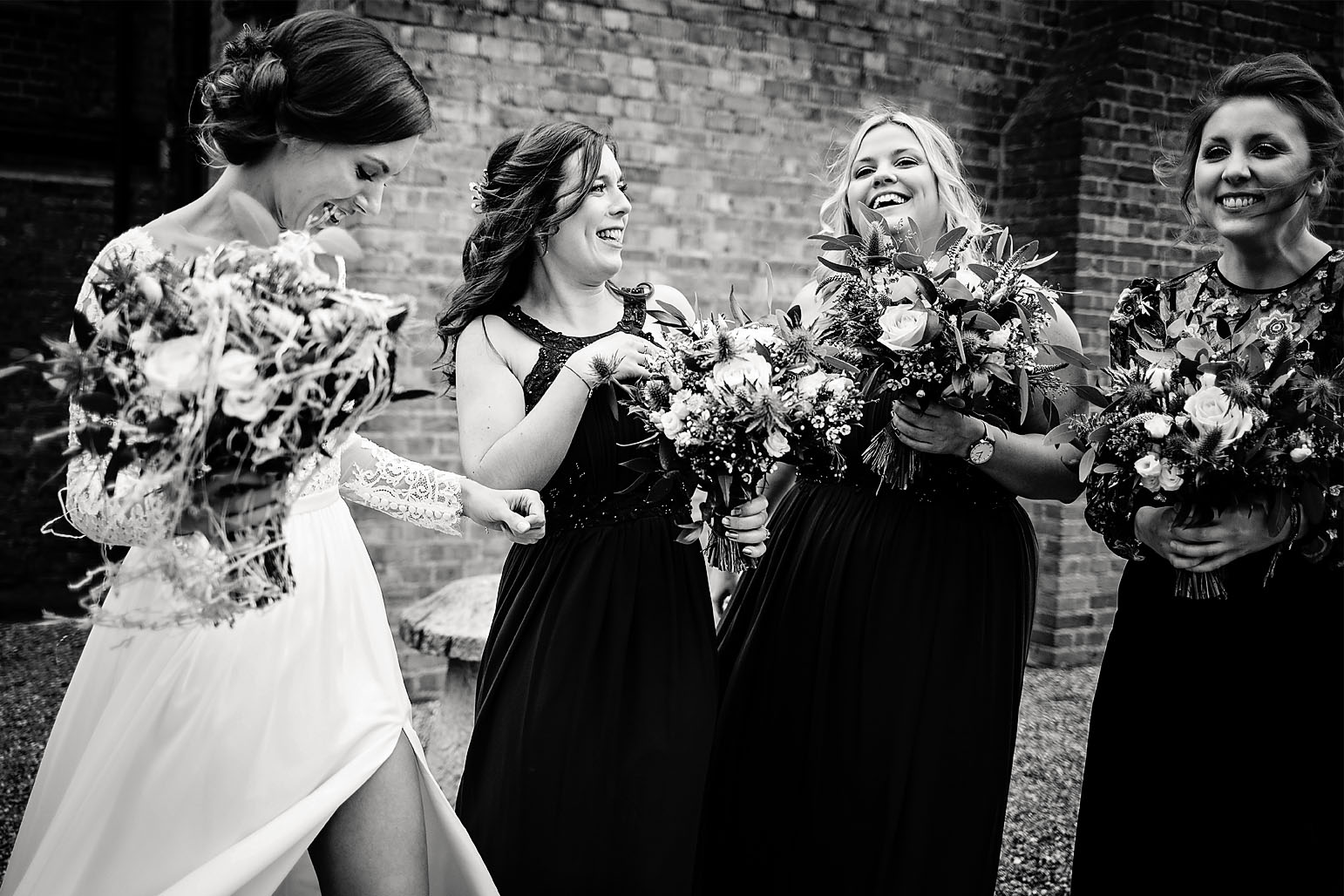 Candid image of Bride and bridesmaids laughing