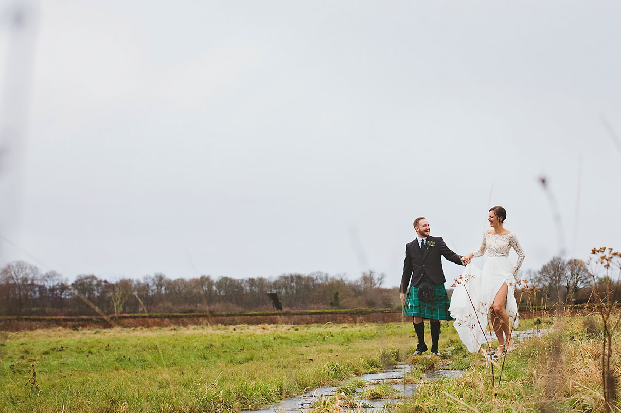 Candid image of bride and groom holding hands, laughing at Lillibrooke Manor and Barns