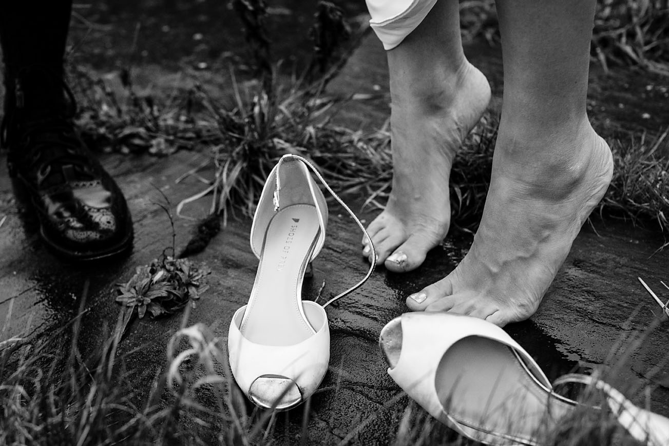 Detail shot of bride's bear feet and and her shoes during couple shoot at Lillibrooke Manor and Barns
