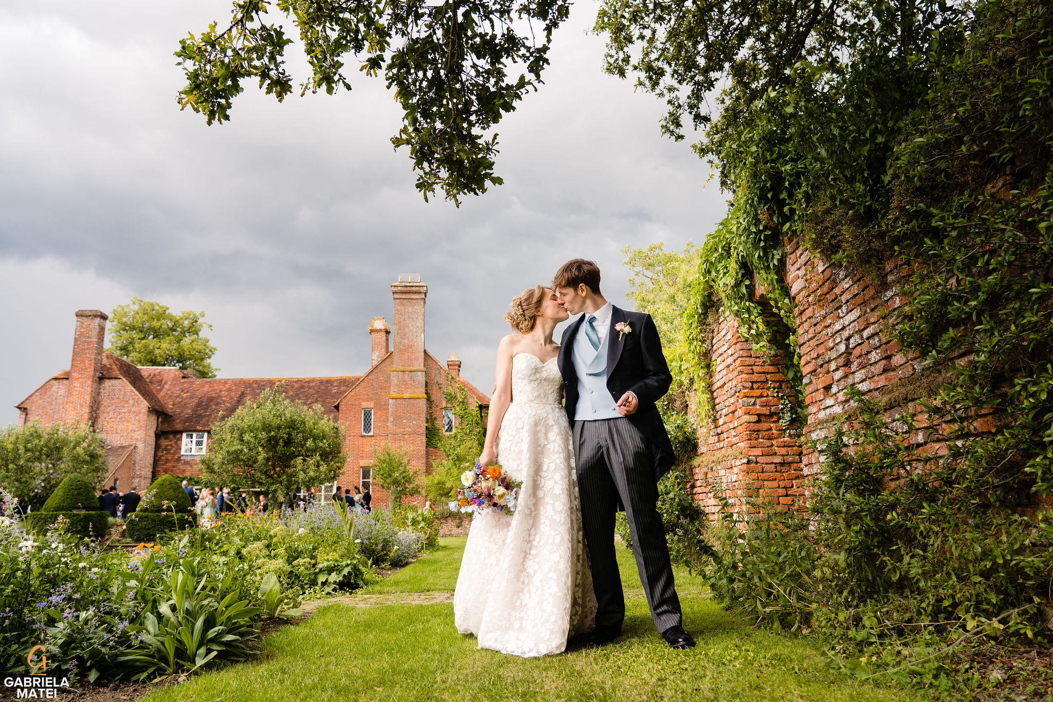 Gorgeous photo of bride and groom kissing in Bore Place garden with Bore Place House in the background at Bore Place wedding by gabriela matei